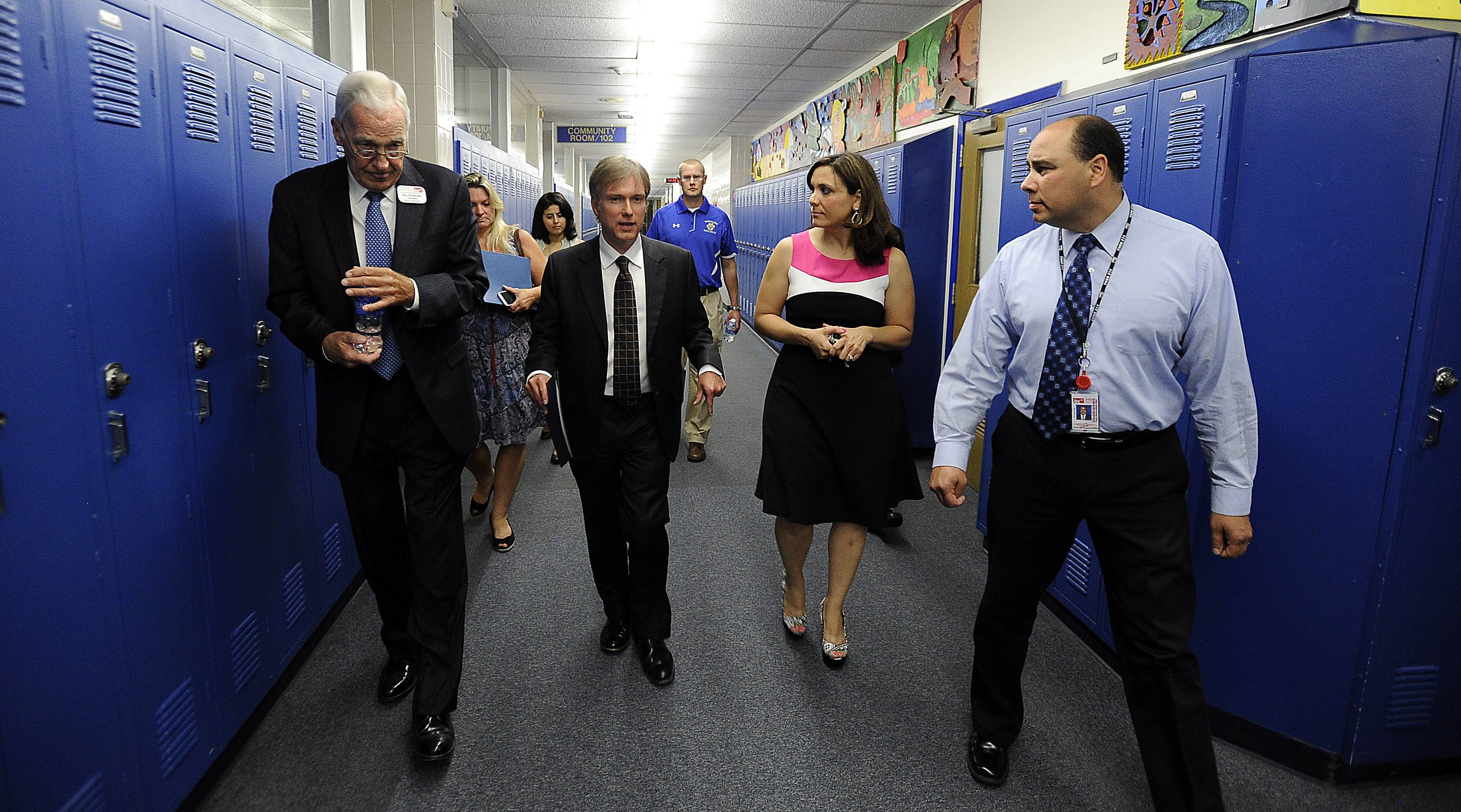 Visiting MP Henry Smith, center, walks the hallway with Bill Dussling, president of the District 214 school board, left, Principal Angela Sisi and Lazaro Lopez, associate superintendent for teaching and learning.