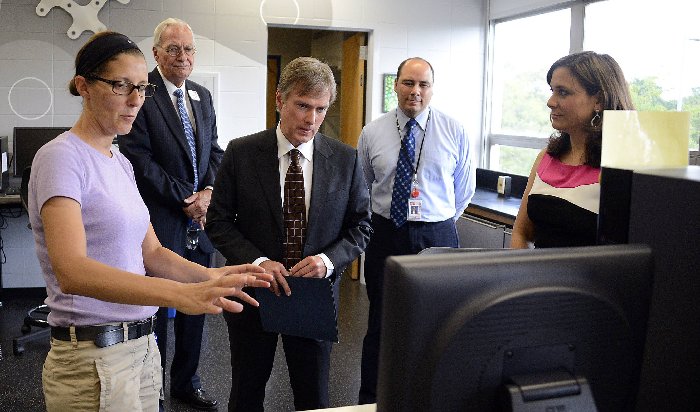 Lisa del Muro, who works in Wheeling High School's nanotechnology department, explains the workings of the lab to Henry Smith, center, with Bill Dussling, president of the District 214 school board, back left; Associate Superintendent Lazaro Lopez (formerly the Wheeling High School principal) and current Principal Angela Sisi.