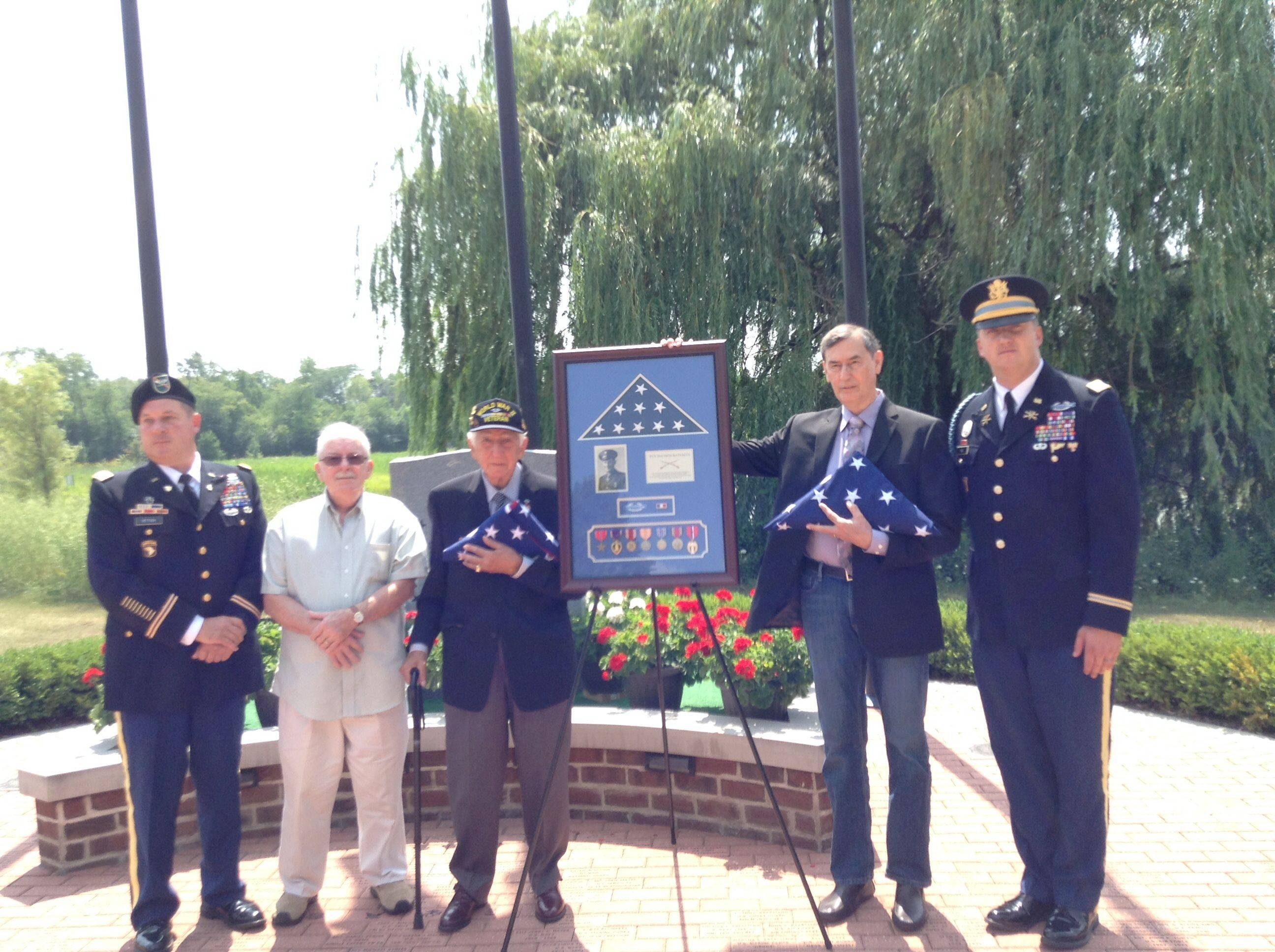 From left, Army Col. Paul J. Hettich, left, Tom McAvoy, former Army Staff Sgt. John Trinca, Thomas Bateman Jr. and Army Cpt. Zachariah Fike at the conclusion of Sunday's ceremony at the College of Lake County Veterans Memorial.