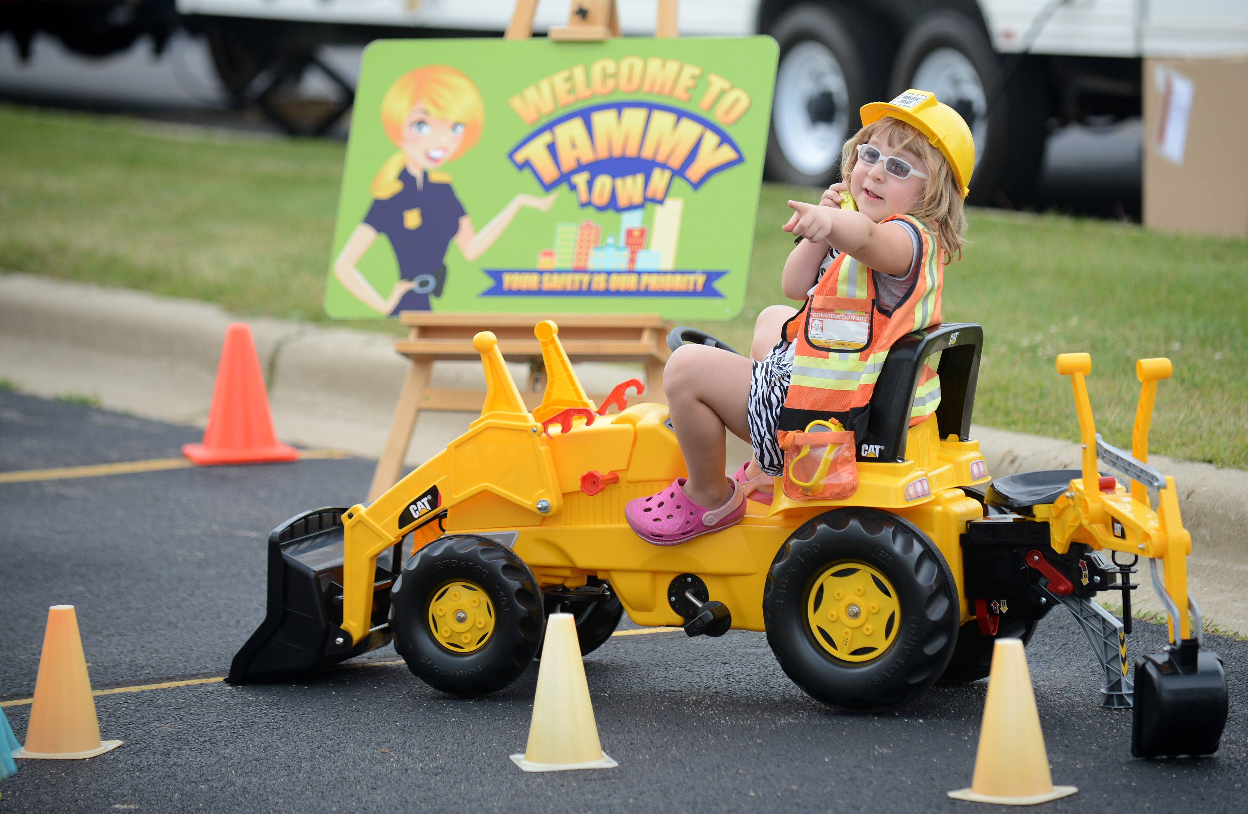 Sydney Sawyer, 4, of South Elgin calls in a 911 call to the police while acting the part of a construction worker in the Tammy Town interactive game for kids at South Elgin's National Night Out event .The program is Bartlett police Officer Tammy Schulz's creation.