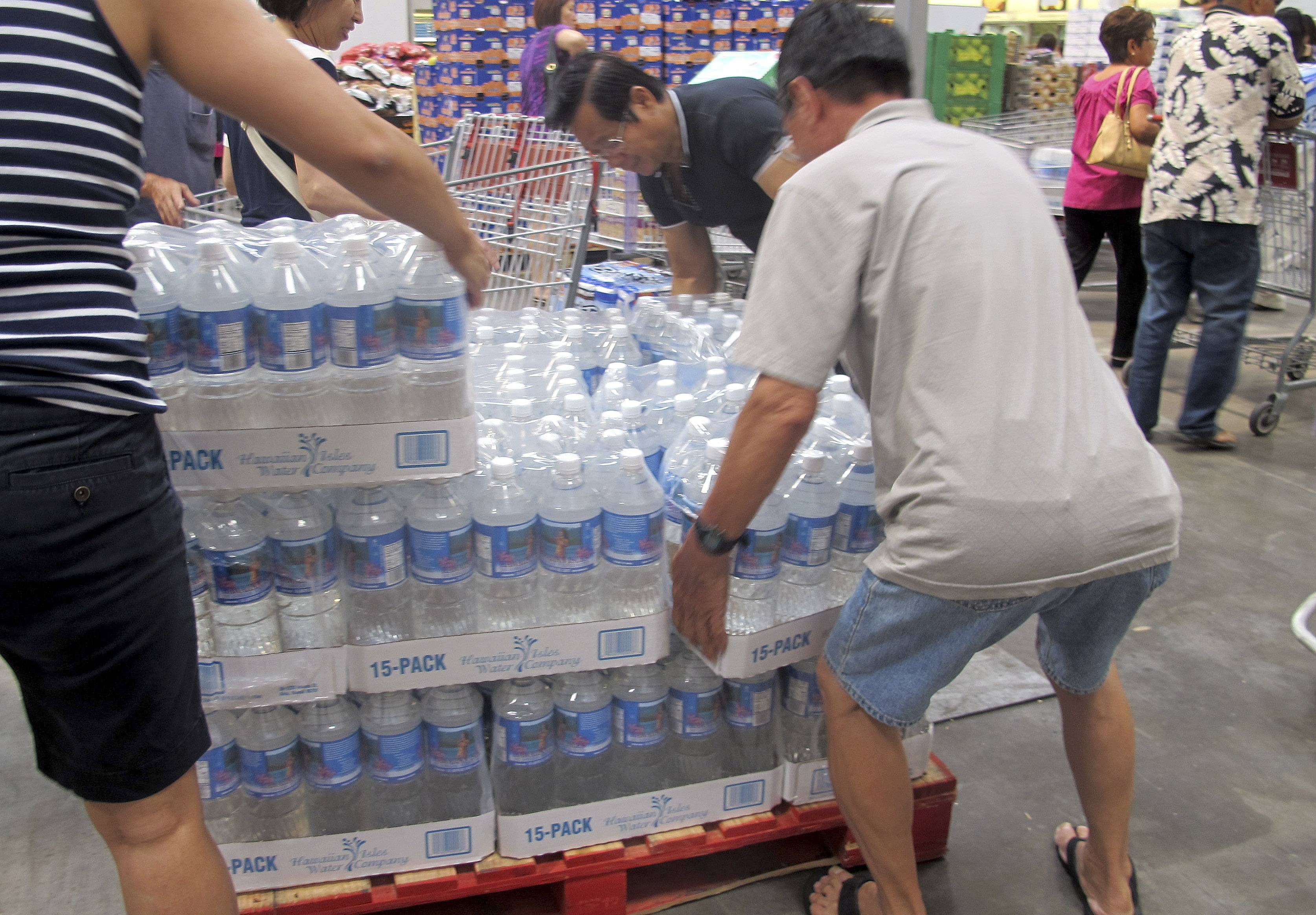 Shoppers grab cases of bottled water Tuesday in preparation for a hurricane and tropical storm heading toward Hawaii at the Iwilei Costco in Honolulu.