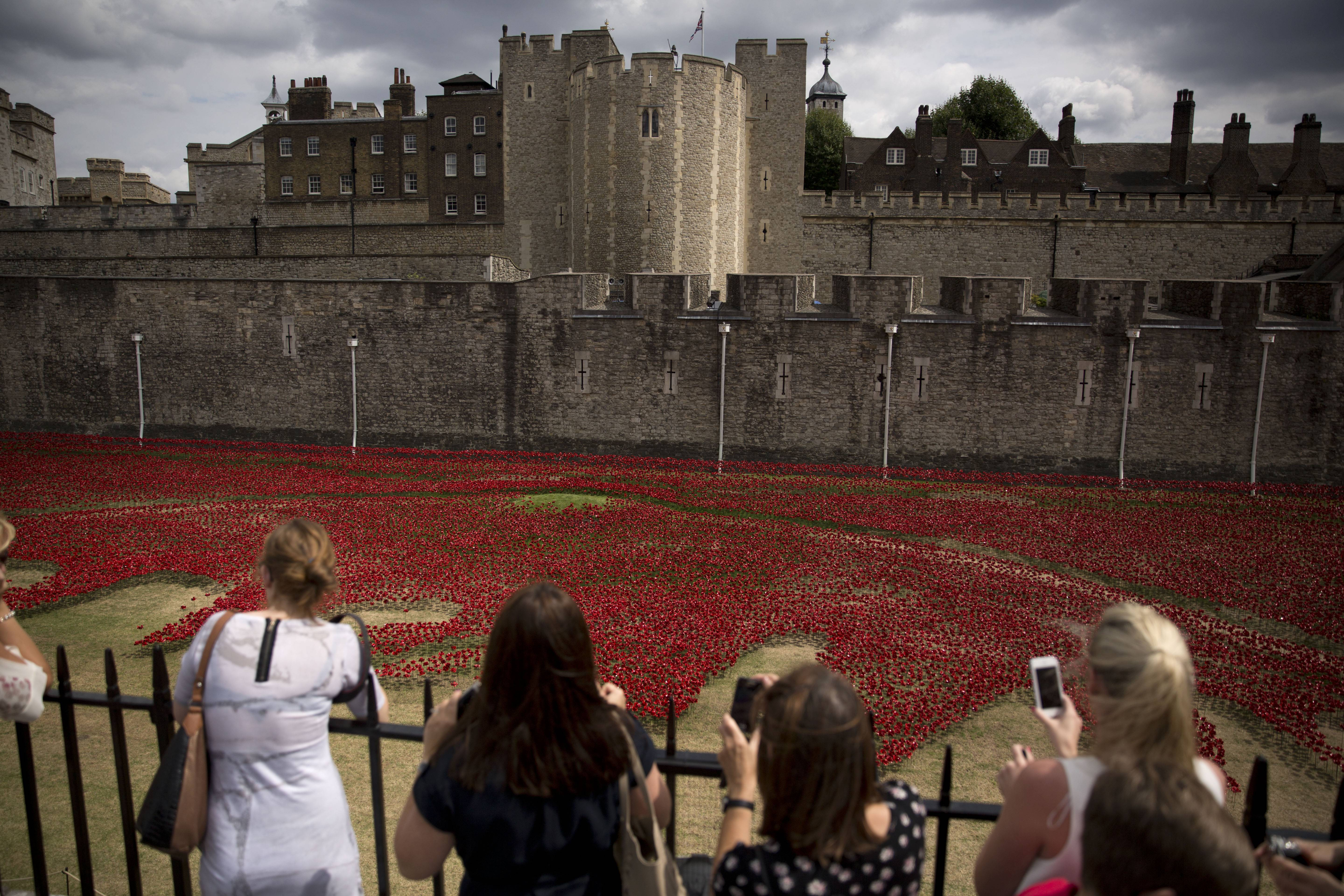 People take pictures Tuesday of a ceramic poppy art installation by artist Paul Cummins entitled 'Blood Swept Lands and Seas of Red' after its official unveiling in the dry moat of the Tower of London in London.