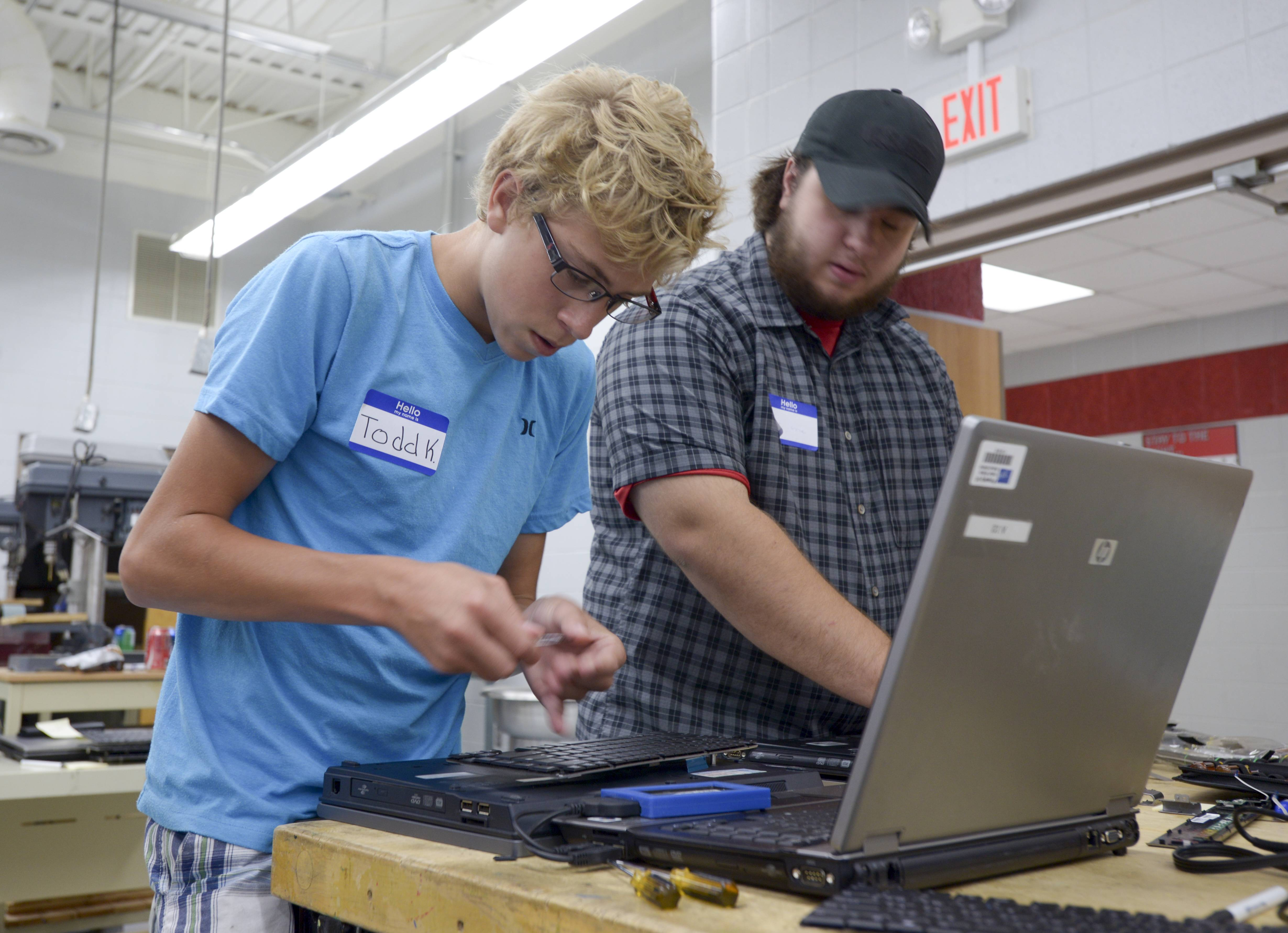 Todd Kuebelbeck, 15, of Naperville and College of DuPage student Kurt Lyne work Tuesday to refurbish laptops no longer in use in Indian Prairie Unit District 204 so they can be given to students in need.