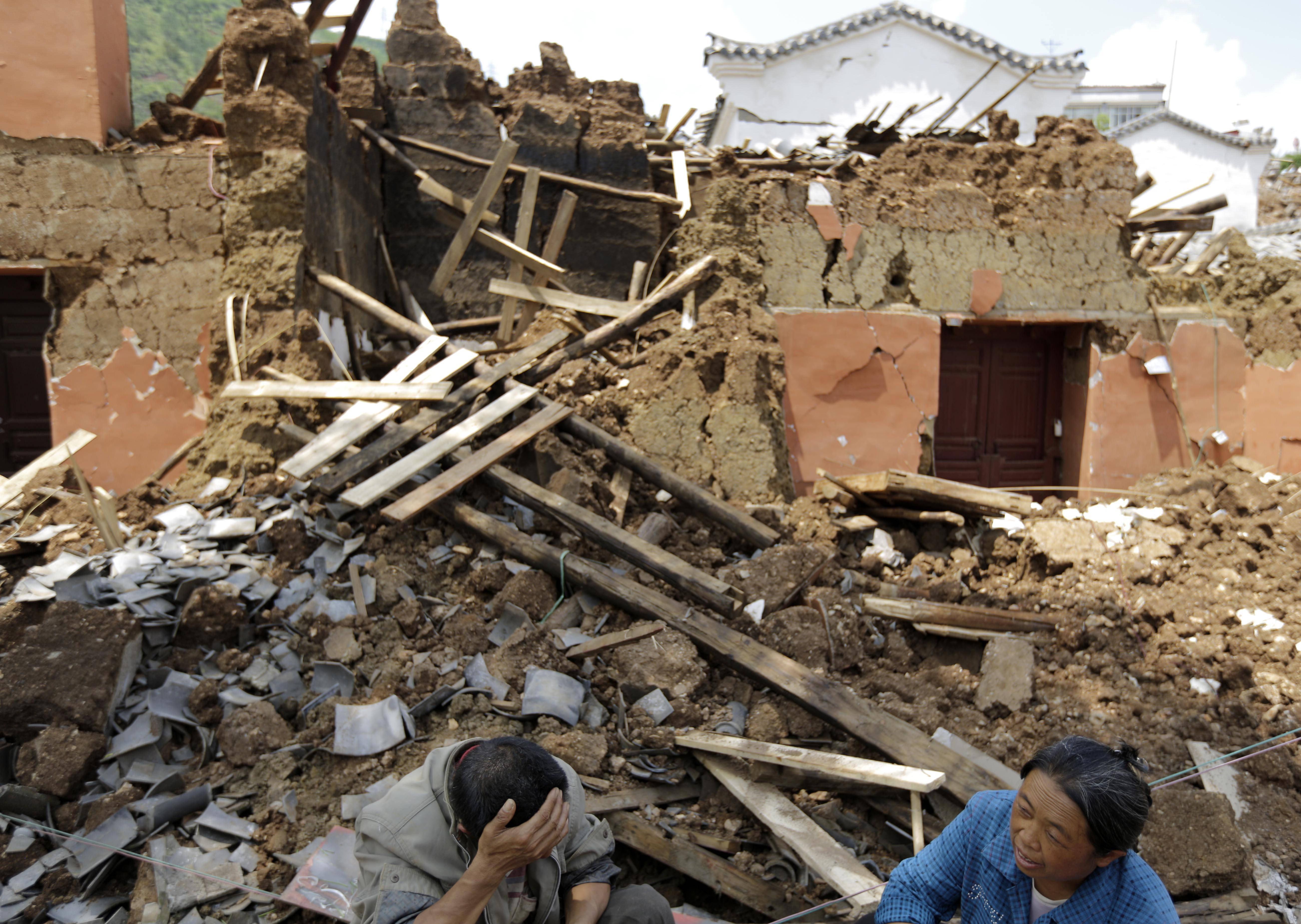 Villagers sit in front of their destroyed house Tuesday following a massive earthquake in the town of Longtoushan in Ludian County in southwest China's Yunnan Province. Rescuers raced Tuesday to evacuate villages near rising lakes formed by landslides, complicating relief efforts following a strong earthquake in southern China that killed more than 300 people and has left thousands homeless.