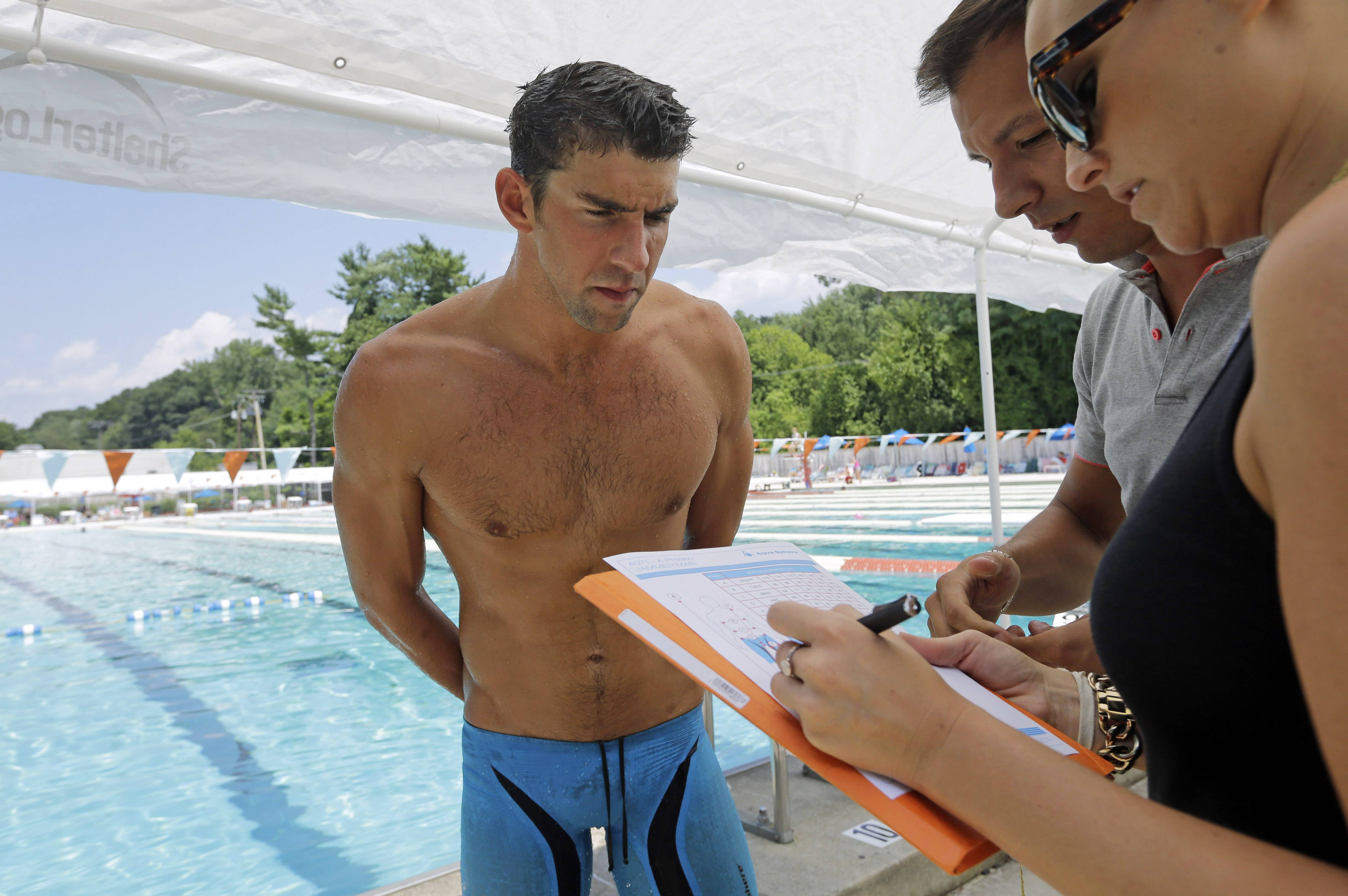 Michael Phelps, left, goes over details of a prototype swimsuit with designers. After partnering with Speedo through most of his swimming career, Phelps has agreed to a new deal with Aqua Sphere.