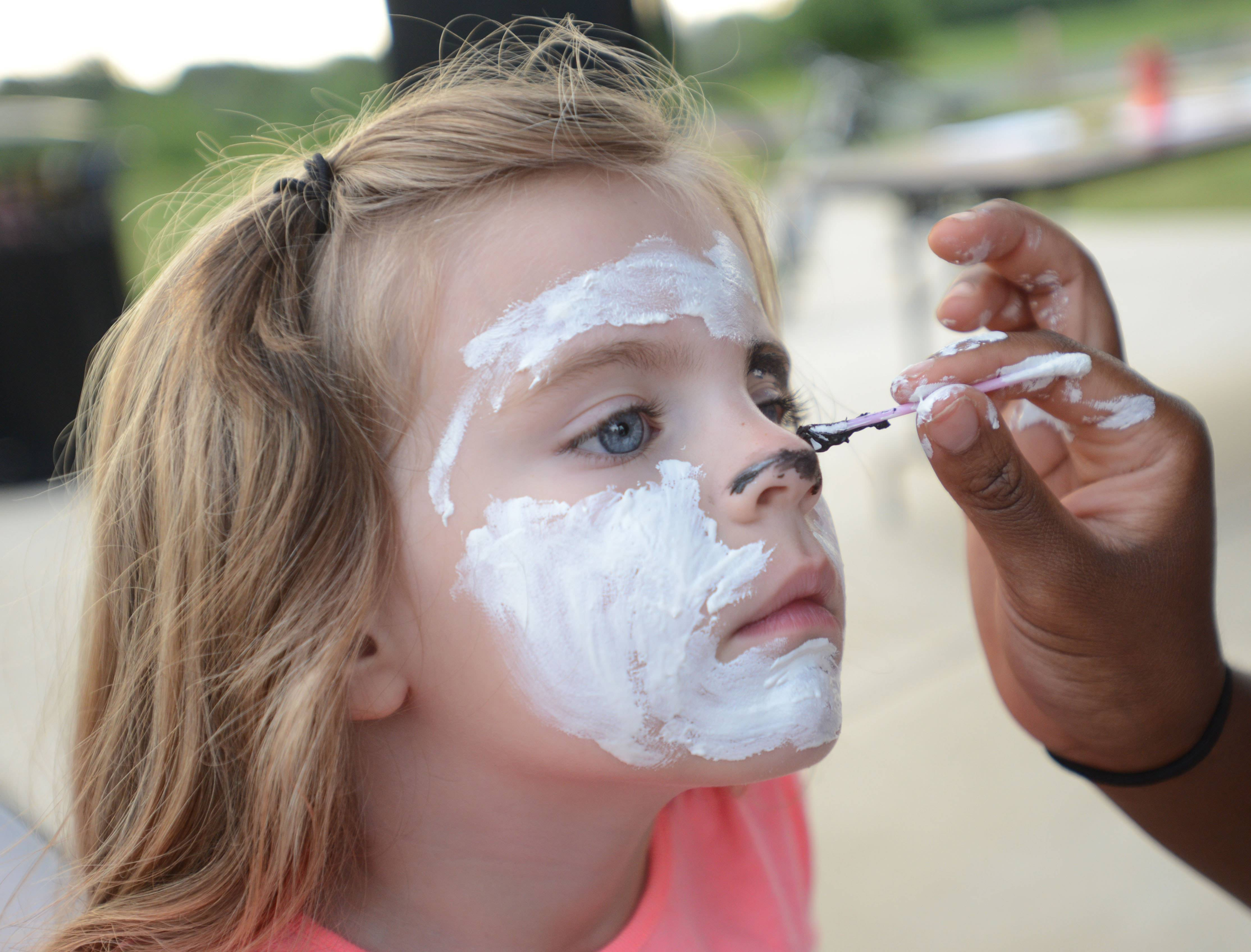 Claire Wolfsmith, 5, of Naperville, gets her face painted like a watchdog Tuesday during National Night Out at Timber Creek Park in Naperville.