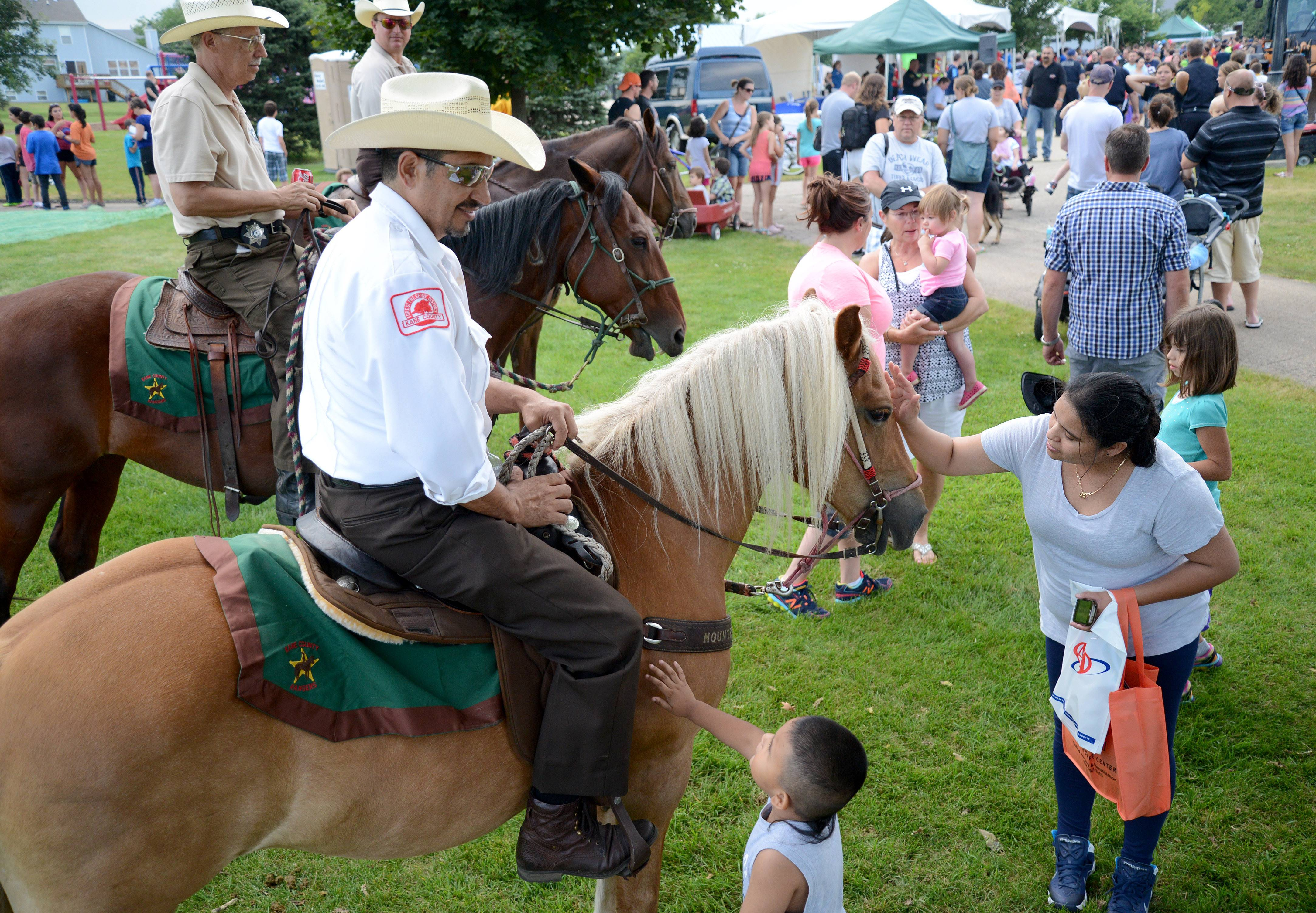 Juan Jasso, 3, and his mother, Jesusita Enriquez, meet Kane County Mounted Ranger Cuper Quintana of Aurora and his horse, Summer, at South Elgin's National Night Out event at Jim Hansen Park on Tuesday night. The mother and son have been coming to the event for three years, and she says seeing the horses is always Juan's first stop at the event. Quintana has been a ranger for eight years.