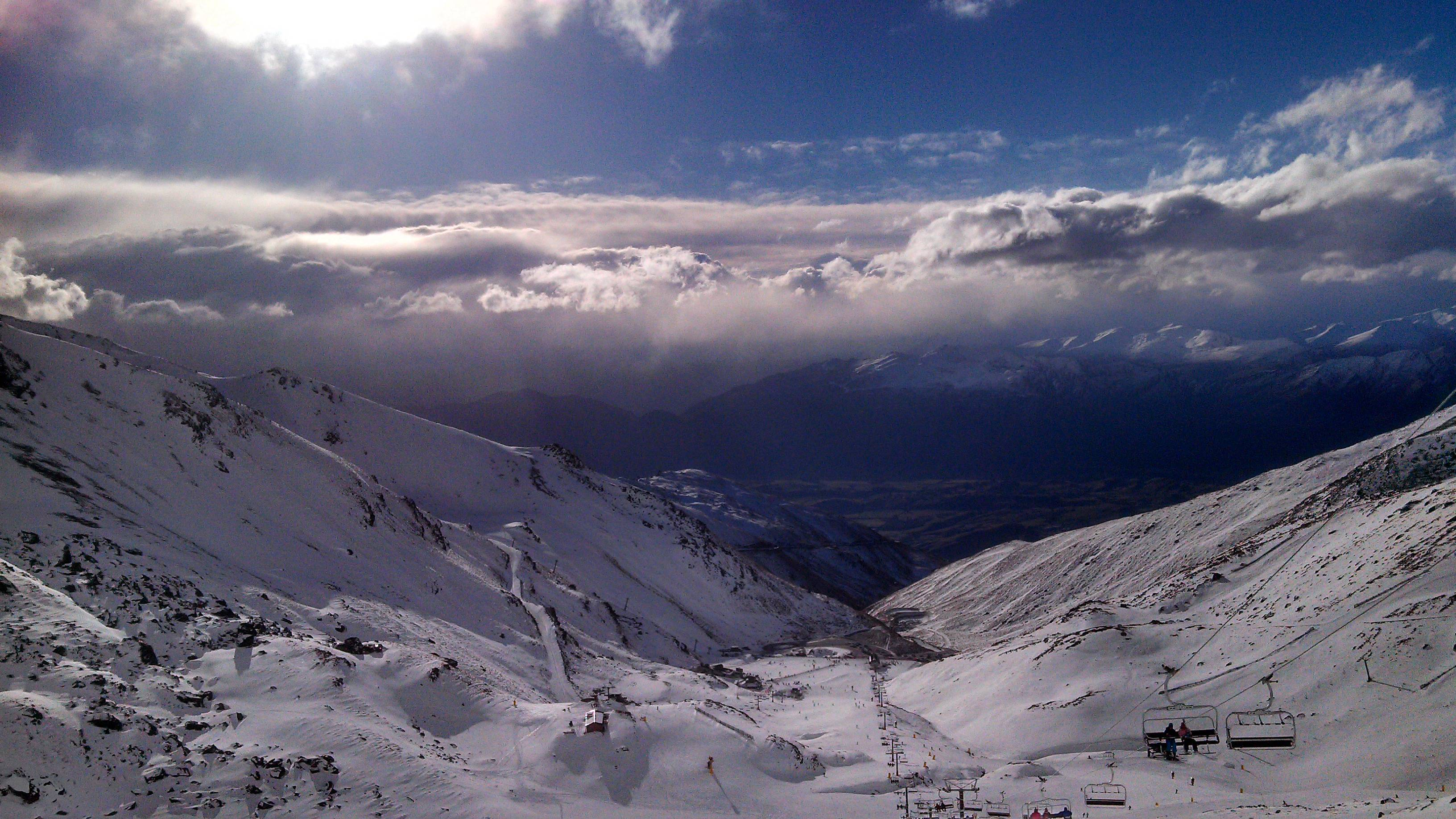 Skiers and snowboarders enjoy clear skies at The Remarkables ski area near Queenstown, New Zealand. The Remarkables is one of several large ski areas that has been making snow at record rates.