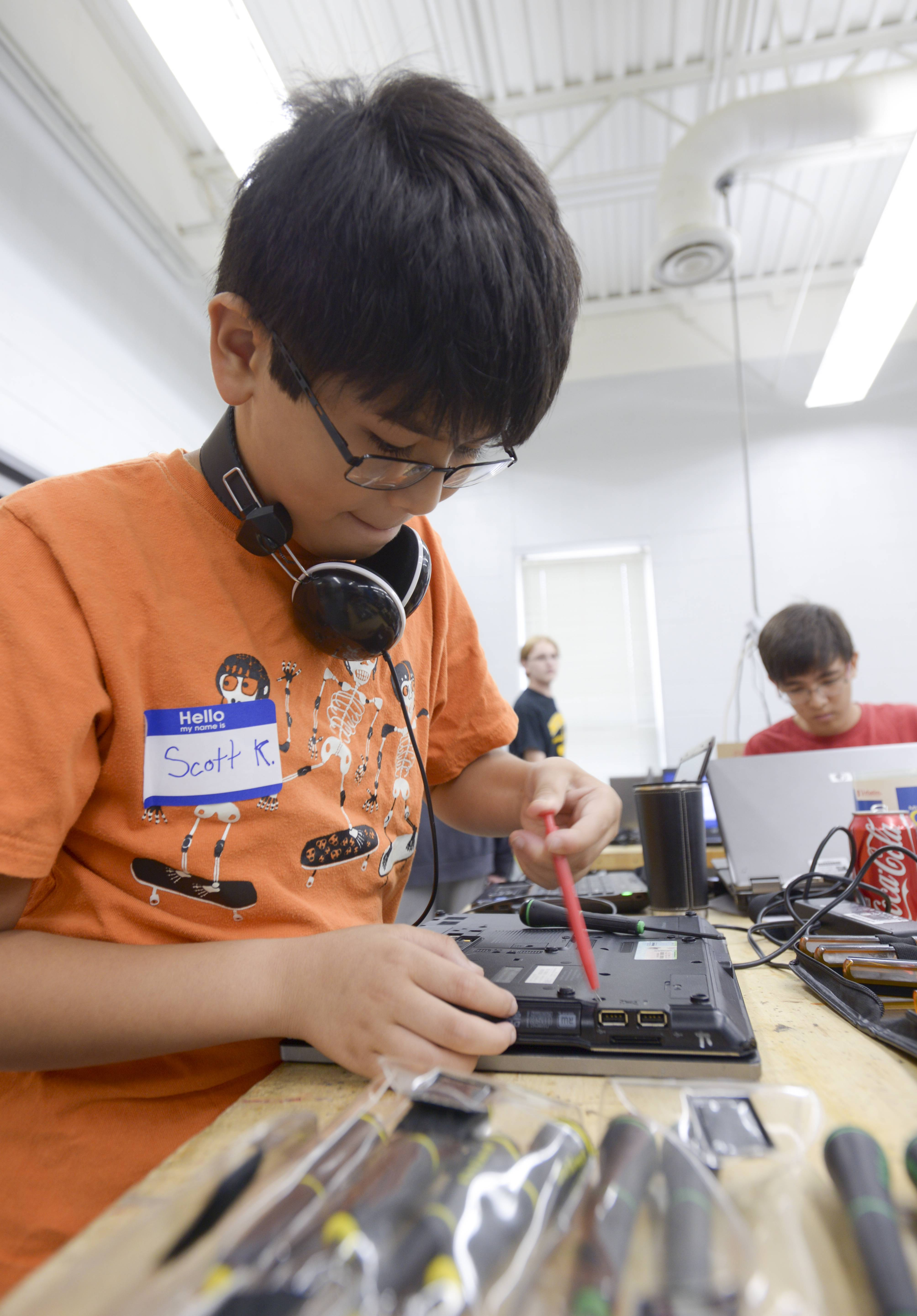 Scott Kwok, 10, of Naperville repairs an old Indian Prairie Unit District 204 laptop the district no longer is using so it can be given to a student in need as part of the Computer Redeployment Program. Volunteers have repaired more than 700 computers since 2008.