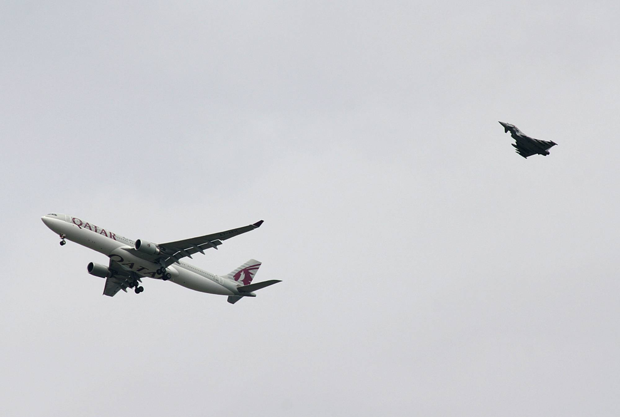 A military fighter jet escorts a passenger jet as it comes in to land at Manchester airport, Manchester, England, Tuesday, Aug. 5, 2014. Police say they have arrested a man on suspicion of making a hoax bomb threat after Qatar Airways Flight 23 landed with a military fighter escort at Britain's Manchester Airport.