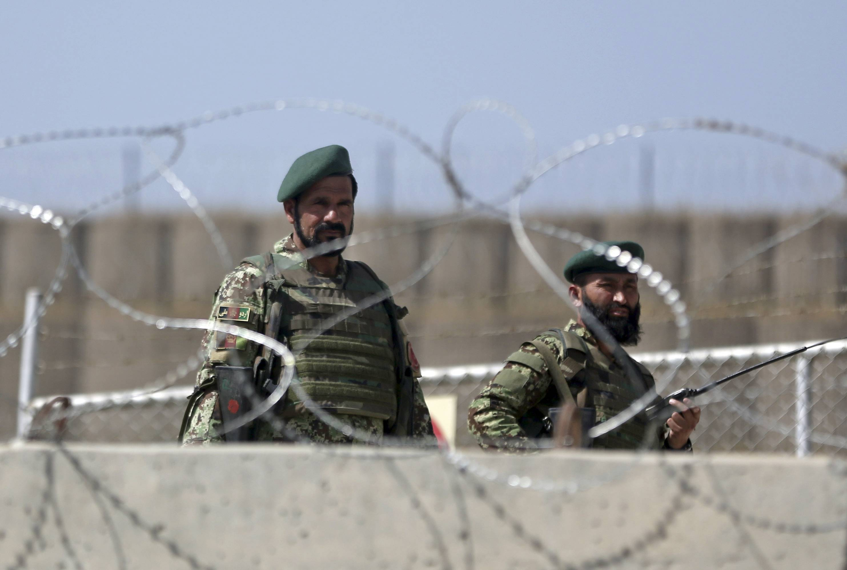 Afghanistan National Army soldiers stand guard at a gate of Camp Qargha, west of Kabul, Afghanistan, Tuesday, Aug. 5, 2014.