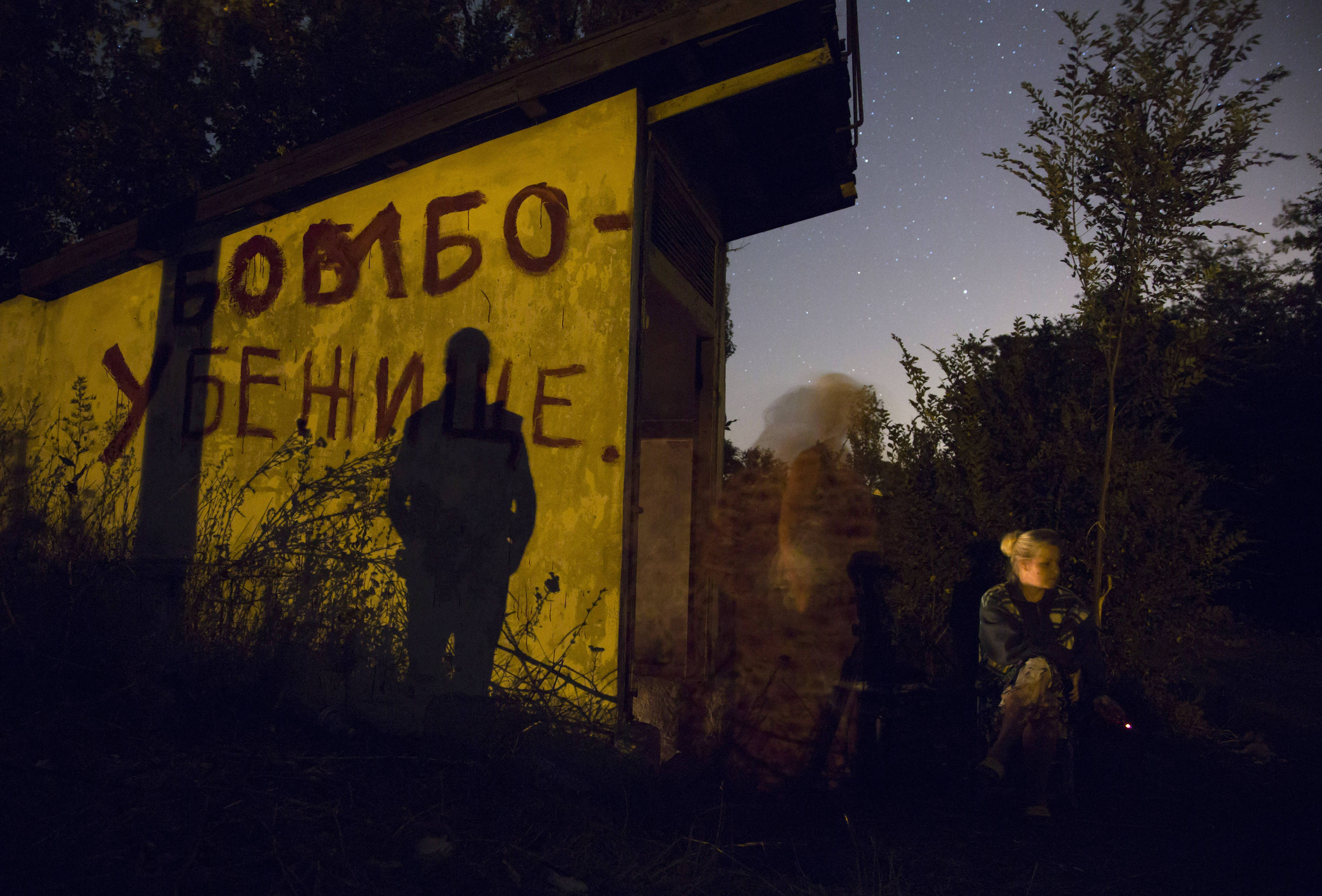 Local residents sit Tuesday near an entrance to a bomb shelter as they exit to get some fresh air during a short cease fire in Petrovsky district in the city of Donetsk.