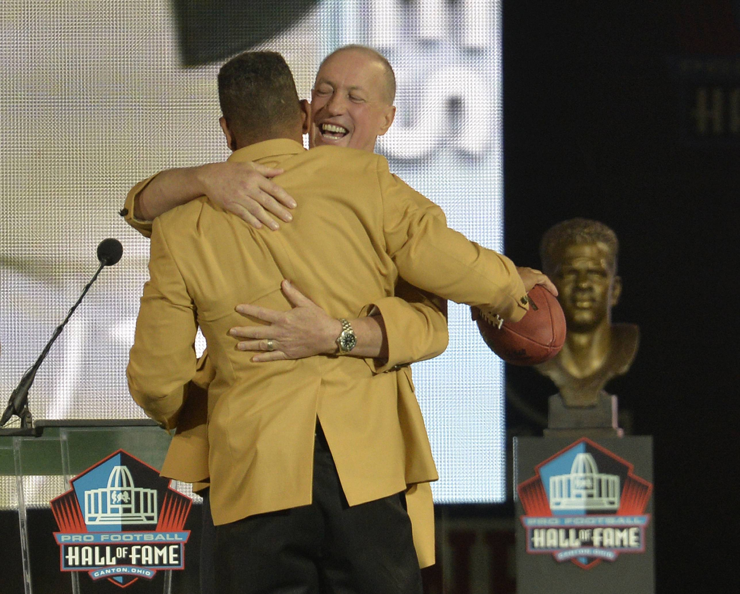 Former Buffalo Bills quarterback Jim Kelly, back, hugs inductee Andre Reed during the Pro Football Hall of Fame enshrinement ceremony Saturday.