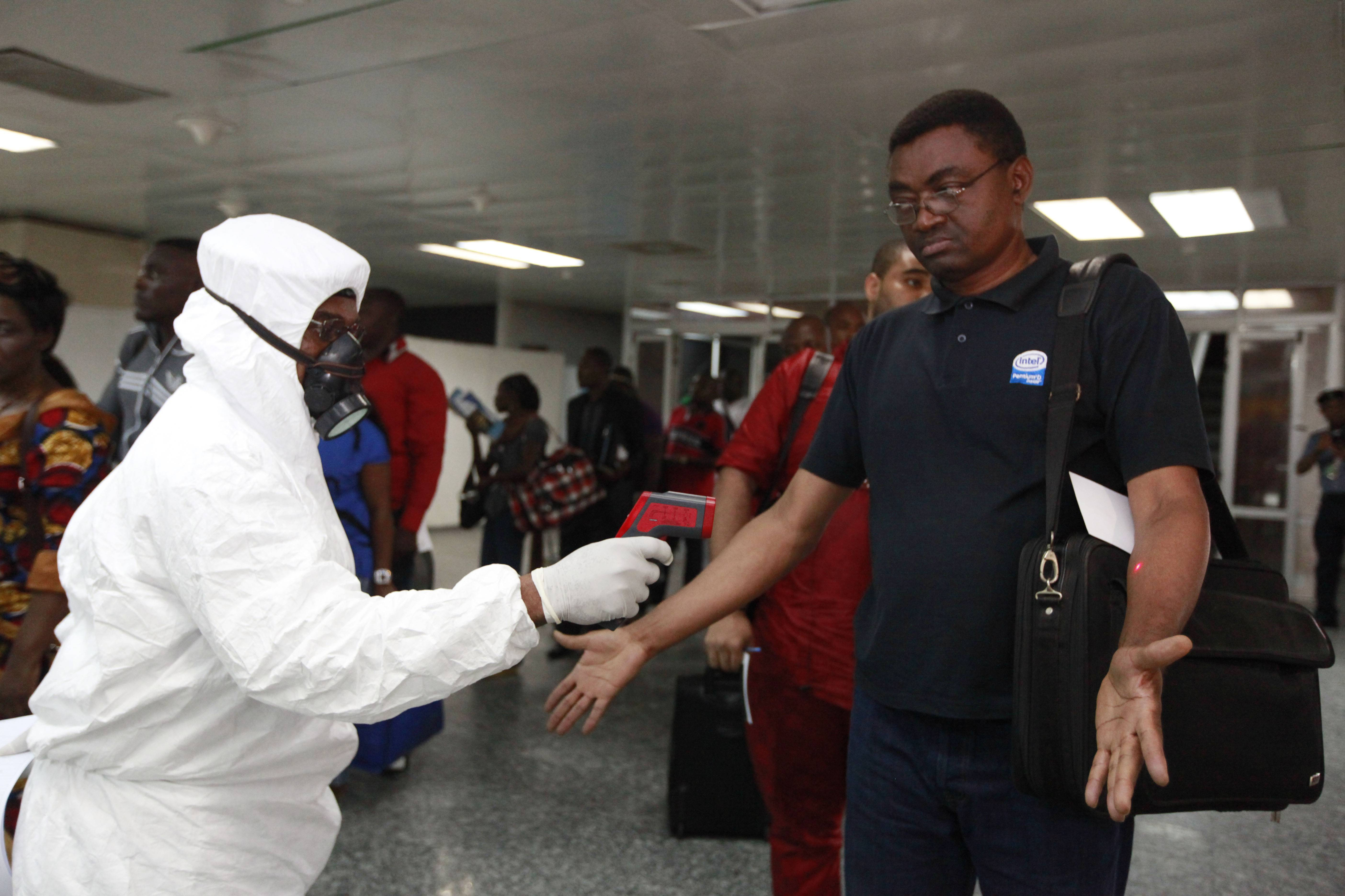 A Nigerian port health official uses a thermometer on a passenger Wednesday at the arrivals hall of Murtala Muhammed International Airport in Lagos, Nigeria. A Nigerian nurse who treated a man with Ebola is now dead and five others are sick with one of the world's most virulent diseases, authorities said Wednesday as the death toll rose to at least 932 people in four West African countries.