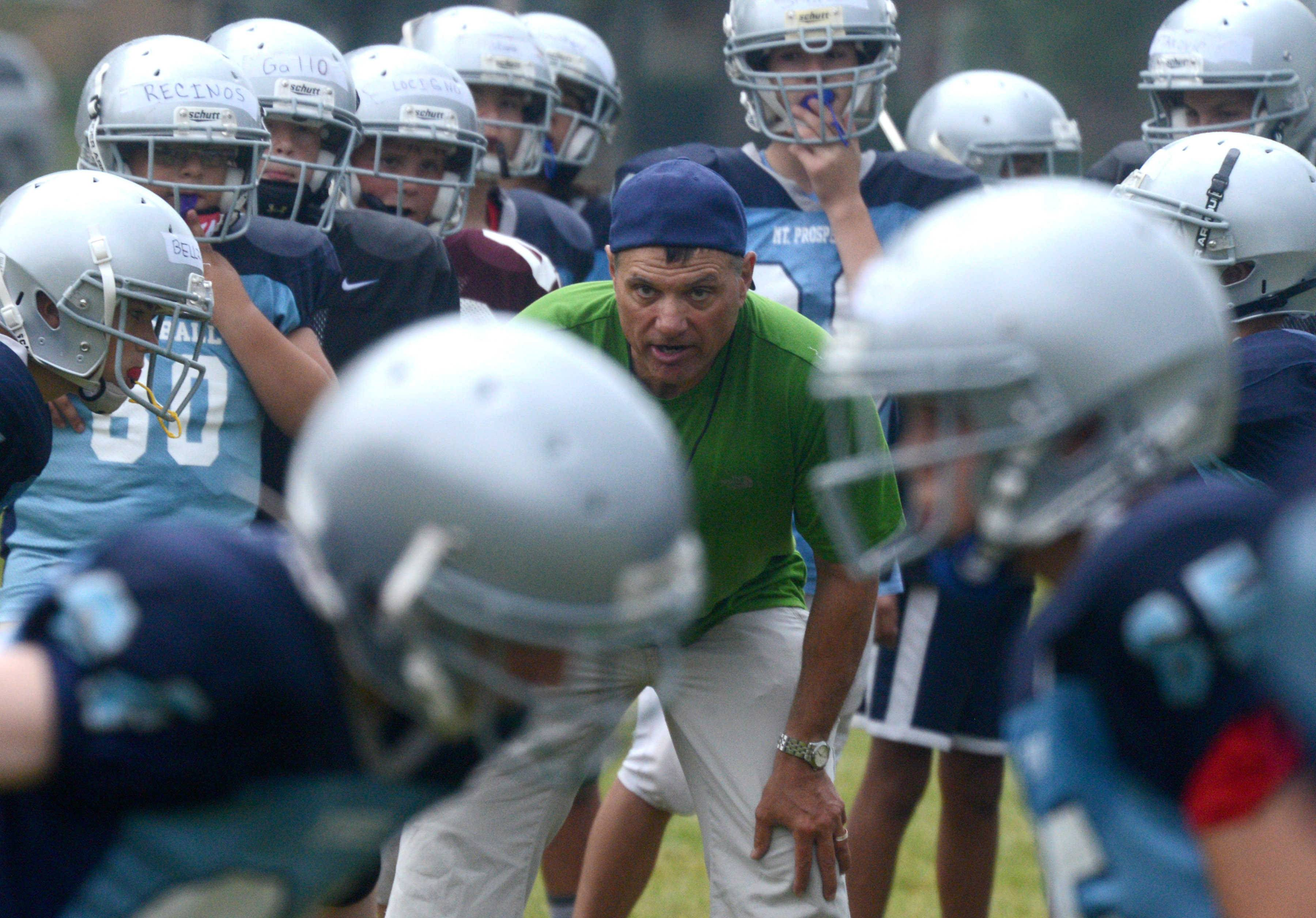 Big Ten-JV level coach Art Fiumetto offers encouragement a during Mount Prospect Youth Football Association practice at Lions Memorial Park in Mount Prospect.