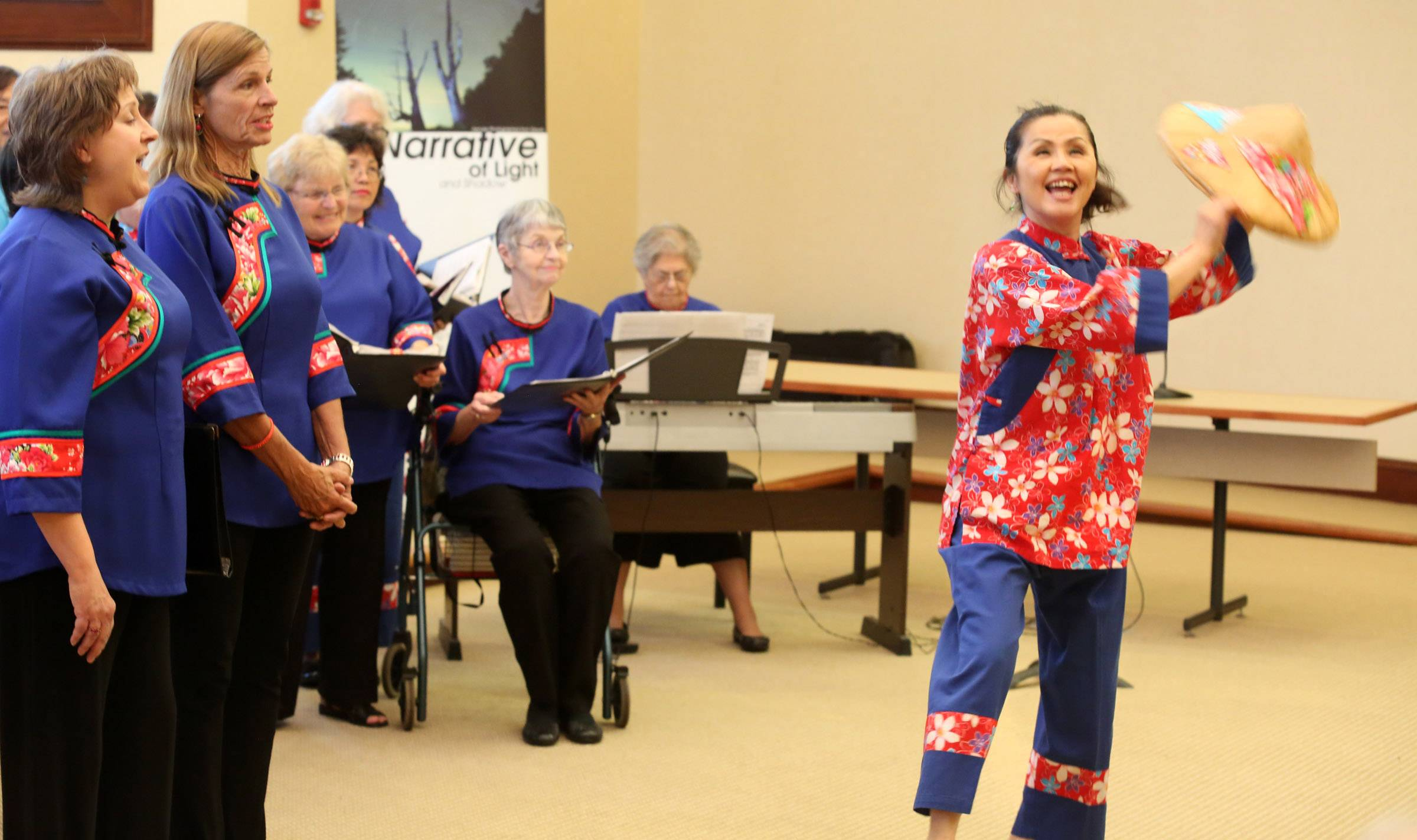 Sherry Yu, of Westmont, captain of the Chicago Hakka Chorus, dances before the crowd at village hall.