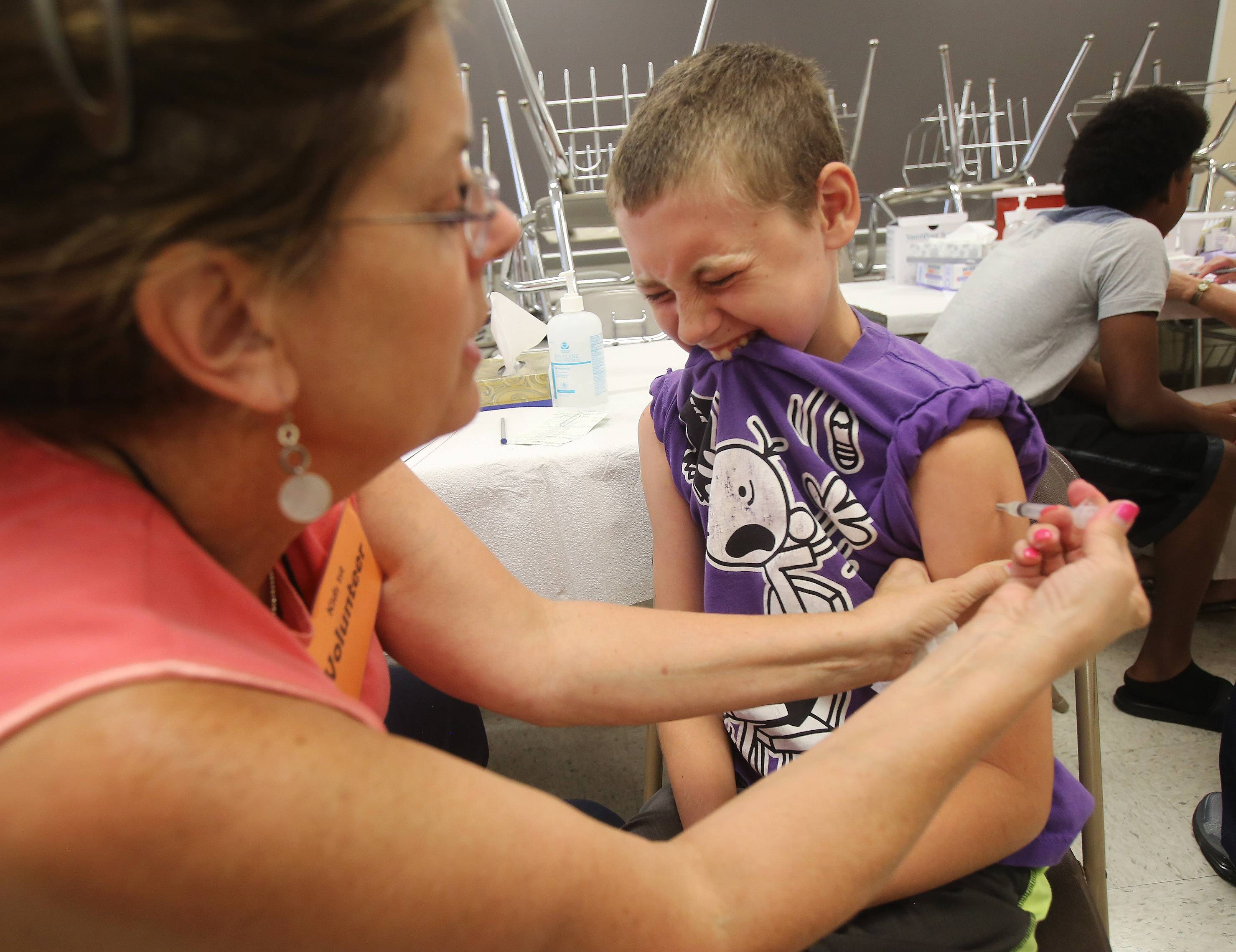 Gavyn Baker, 11, of Wauconda, receives an immunization Wednesday during the final Kids 1st Health Fair in Waukegan. Organizers are ending the program after 21 years.