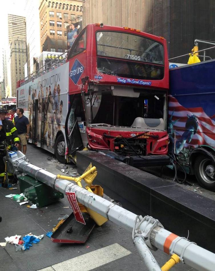 Emergency personnel respond to a collision between two double-decker buses on New York City's Times Square, Tuesday, Aug. 5, 2014. The Theater District accident injured 13 people, three of them seriously.
