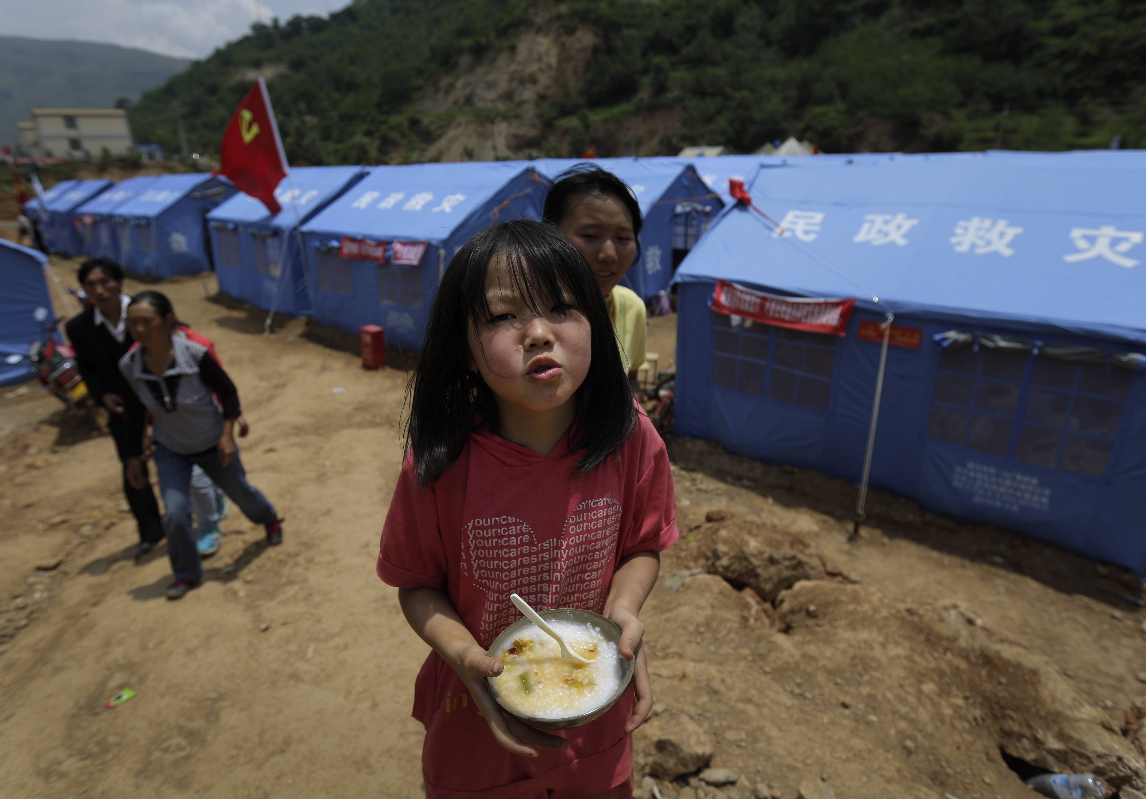 A child holds a bowl of porridge cooked by volunteers in front of temporary tents set up at the quake-hit area in the town of Longtoushan in Ludian county in southwest China's Yunnan Province Wednesday, Aug. 6, 2014. Some 10,000 troops and hundreds of volunteers have rushed to Ludian to clear roads and dig out survivors from the debris, but landslides and bouts of heavy rains have complicated the efforts. (