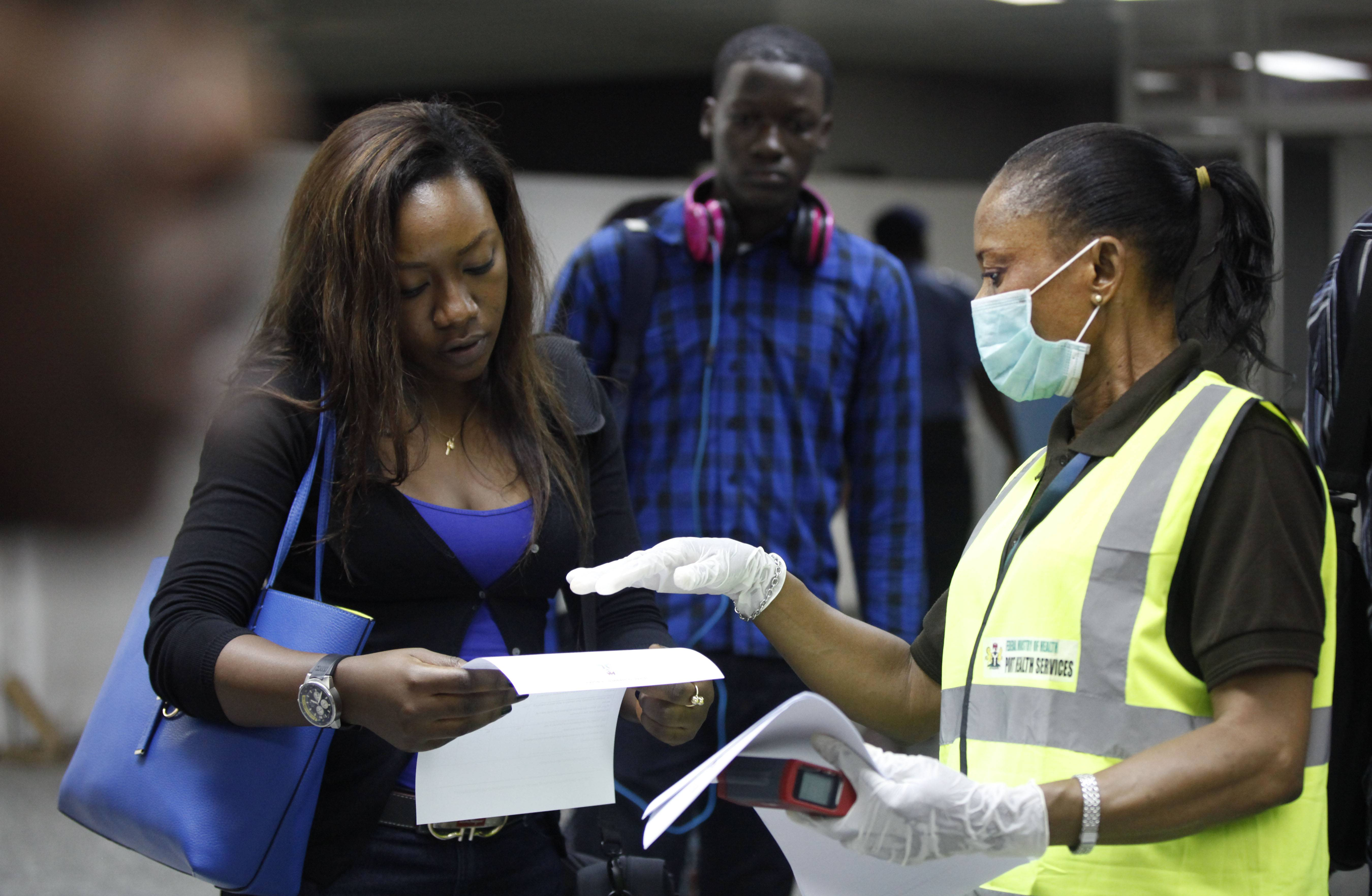 A Nigerian port health official speaks to a passenger Wednesday at the arrivals hall of Murtala Muhammed International Airport in Lagos, Nigeria. A Nigerian nurse who treated a man with Ebola is now dead and five others are sick with one of the world's most virulent diseases, authorities said Wednesday as the death toll rose to at least 932 people in four West African countries.