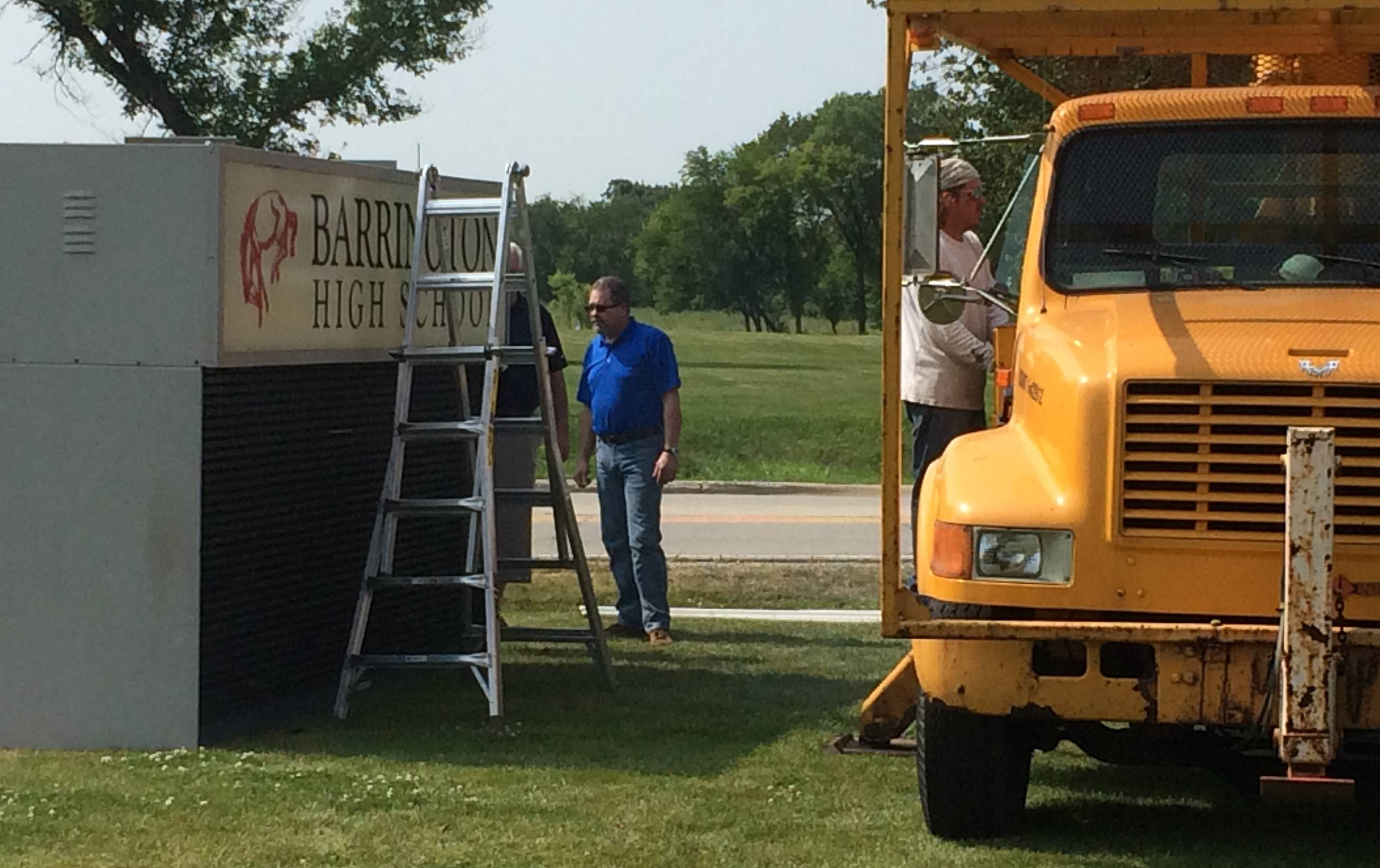 District workers prepare to replace the exterior sign at Barrington High School.