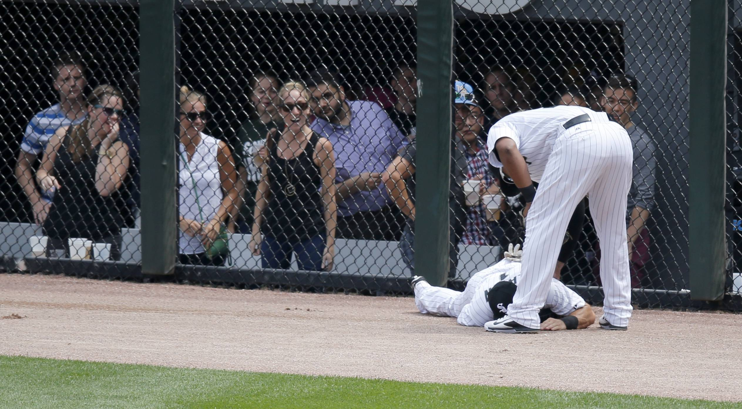 Dayan Viciedo checks on Adam Eaton after Eaton slammed into the fence chasing a 2-run homer by the Rangers' Adam Rosales.
