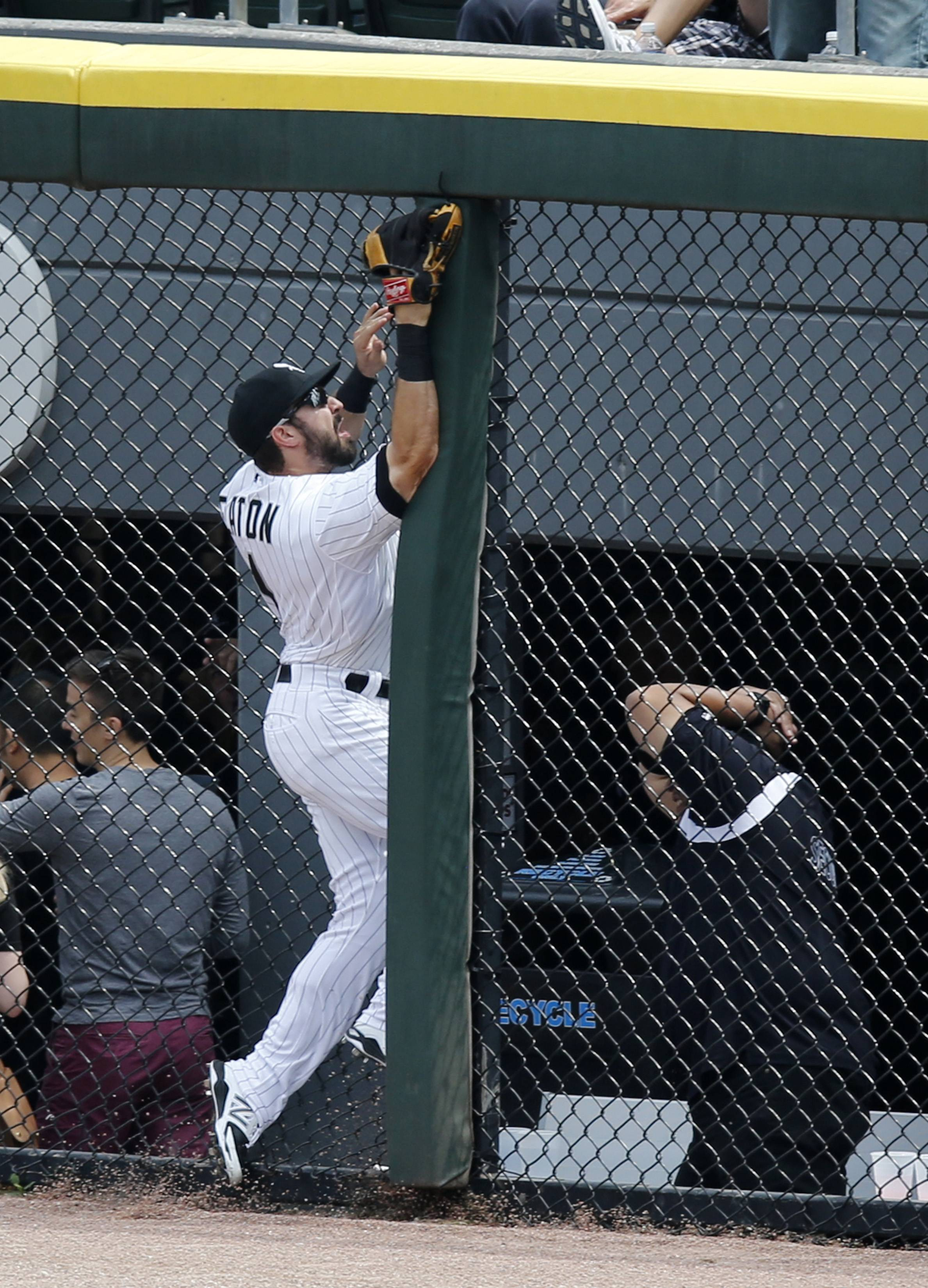 White Sox center fielder Adam Eaton slams into the right center field fence chasing a two-run home run by Texas Rangers' Adam Rosales during the second inning of a baseball game Wednesday.