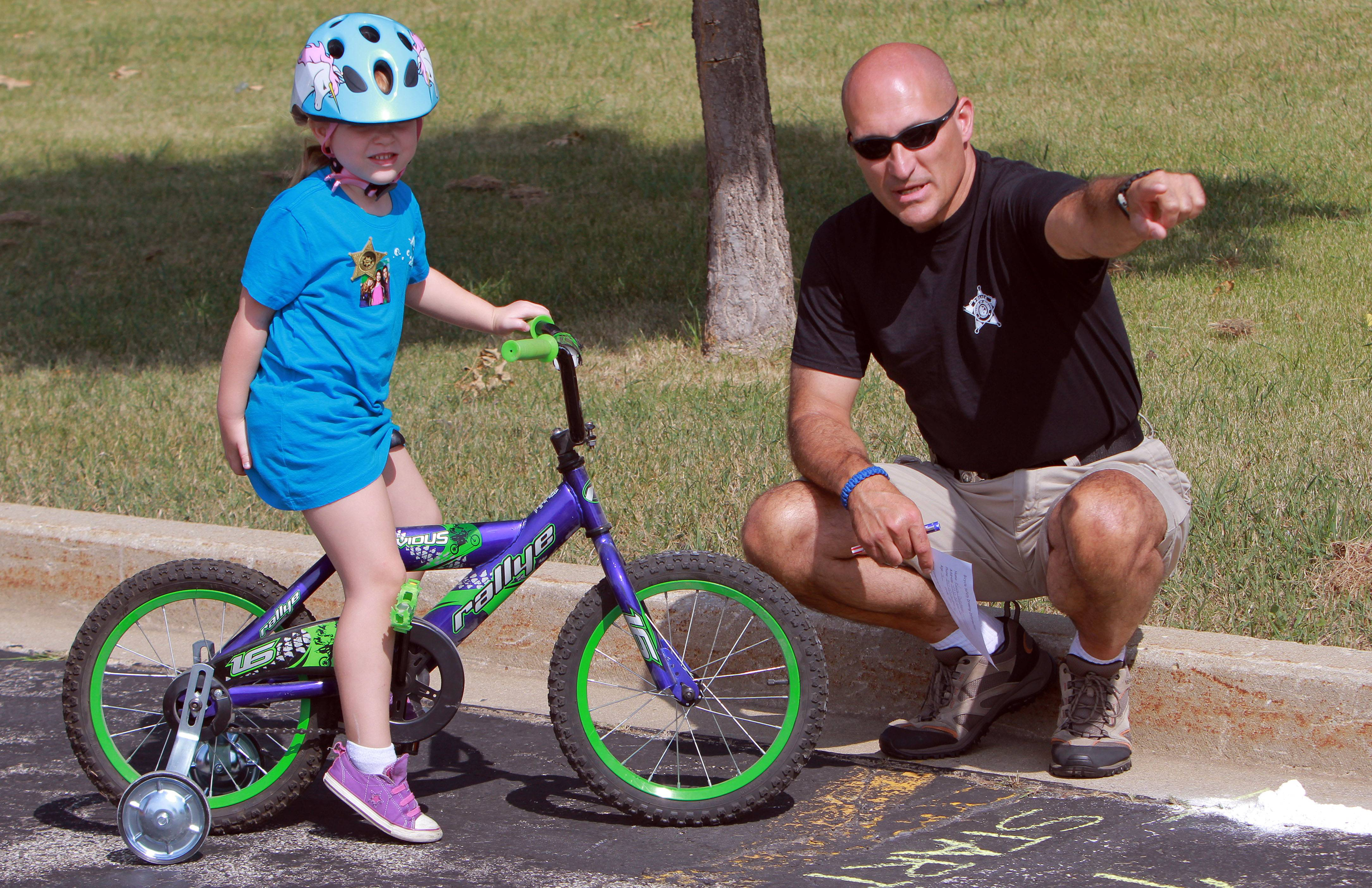 Keira Dallstream, 4, of Gurnee, gets some pointers from Gurnee Police Officer Marty DePerte during Thursday's bike rodeo at Woodland Middle School in Gurnee.