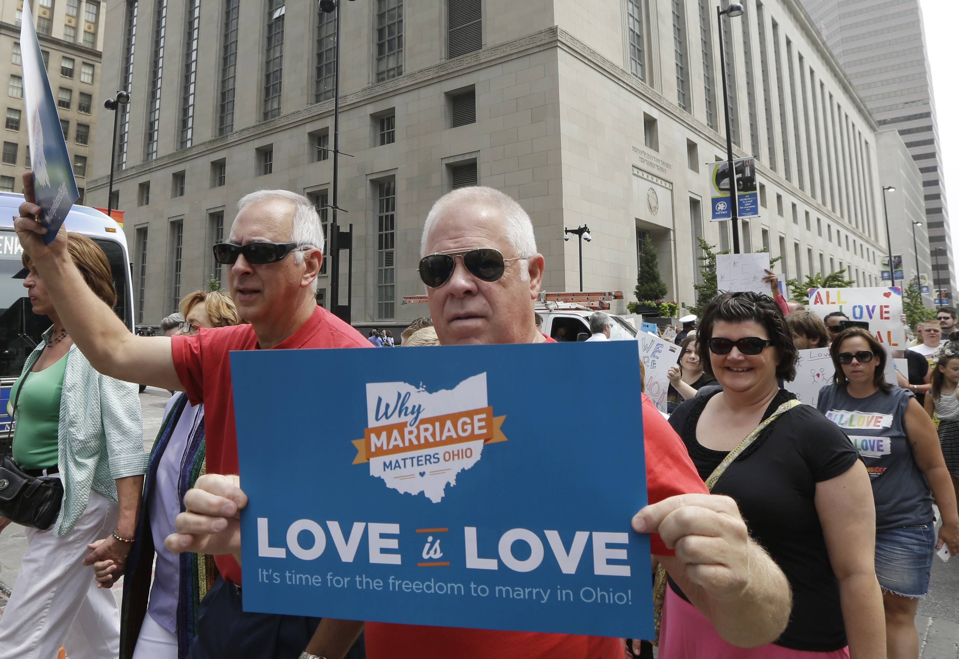 Gay marriage supporters march from the Potter Stewart United States Courthouse, rear, Wednesday, Aug. 6, 2014, to Fountain Square in Cincinnati. Three judges of the 6th U.S. Circuit Court of Appeals in Cincinnati heard arguments Wednesday in six gay marriage fights from four states, Kentucky, Michigan, Ohio and Tennessee.