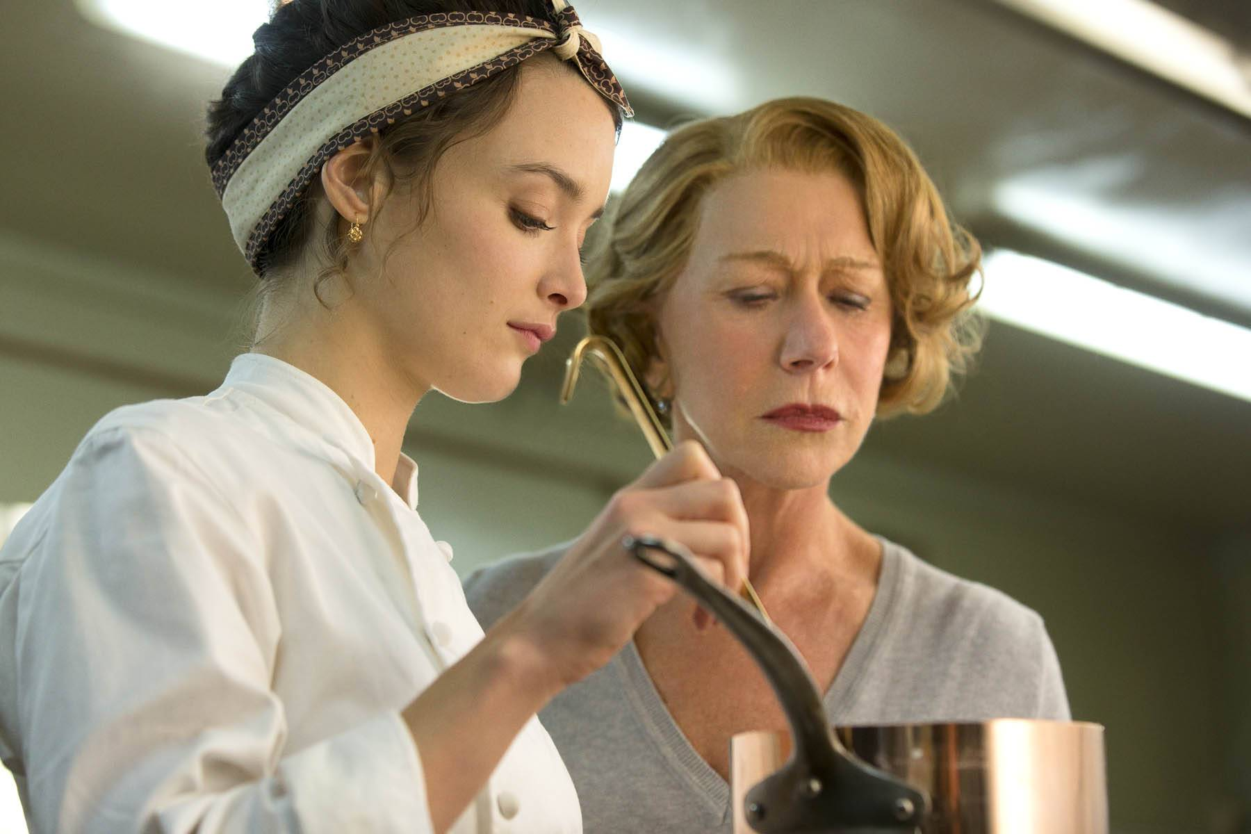 "Marguerite (Charlotte Le Bon) cooks under the watchful eye of Madame Mallory (Helen Mirren) in ""The Hundred-Foot Journey."""