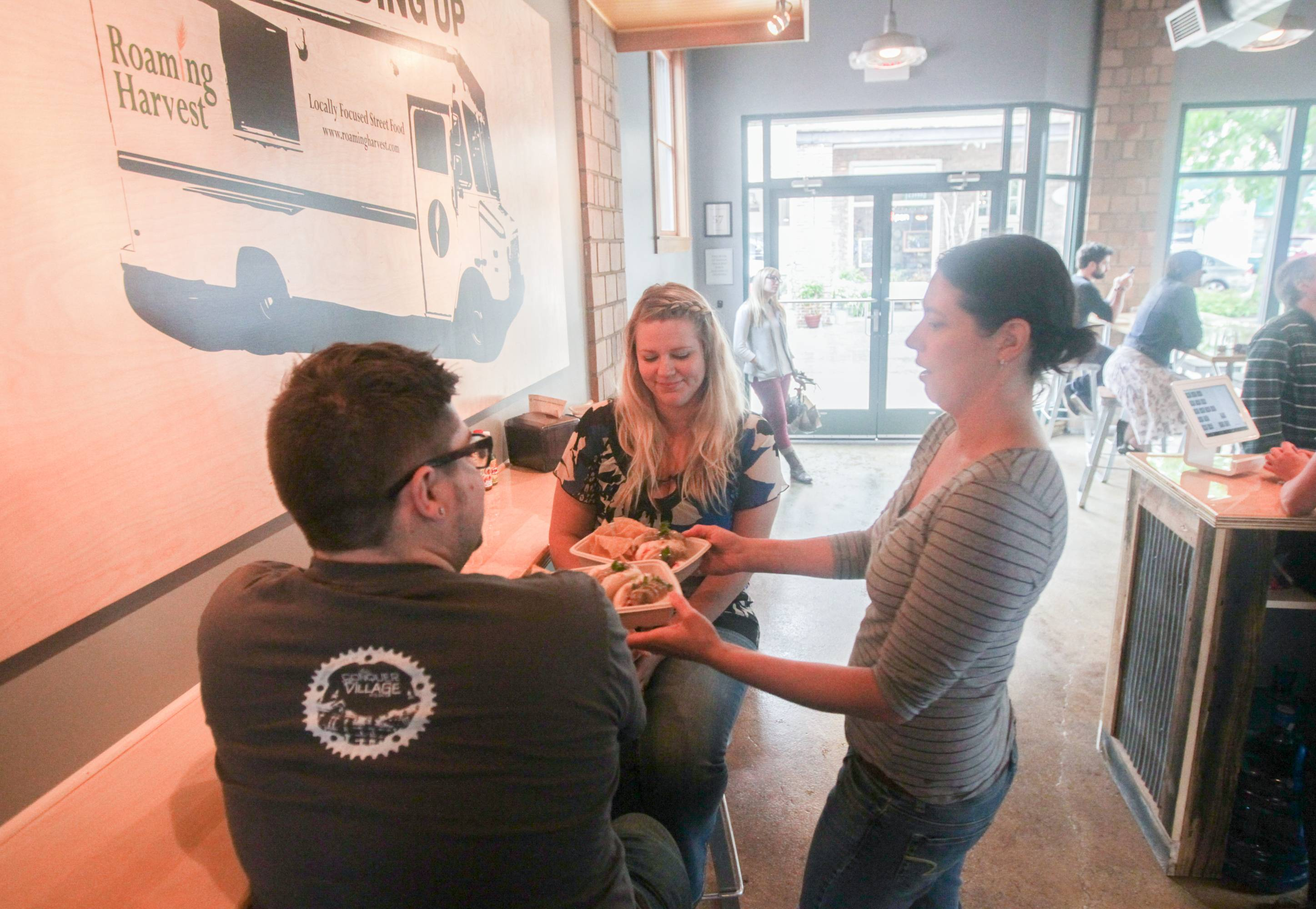 Lance Hill, left, and Chelsea Hill, both of Traverse City, are being served by Rebecca Brown, co-owner at Harvest in downtown Traverse City, Mich.