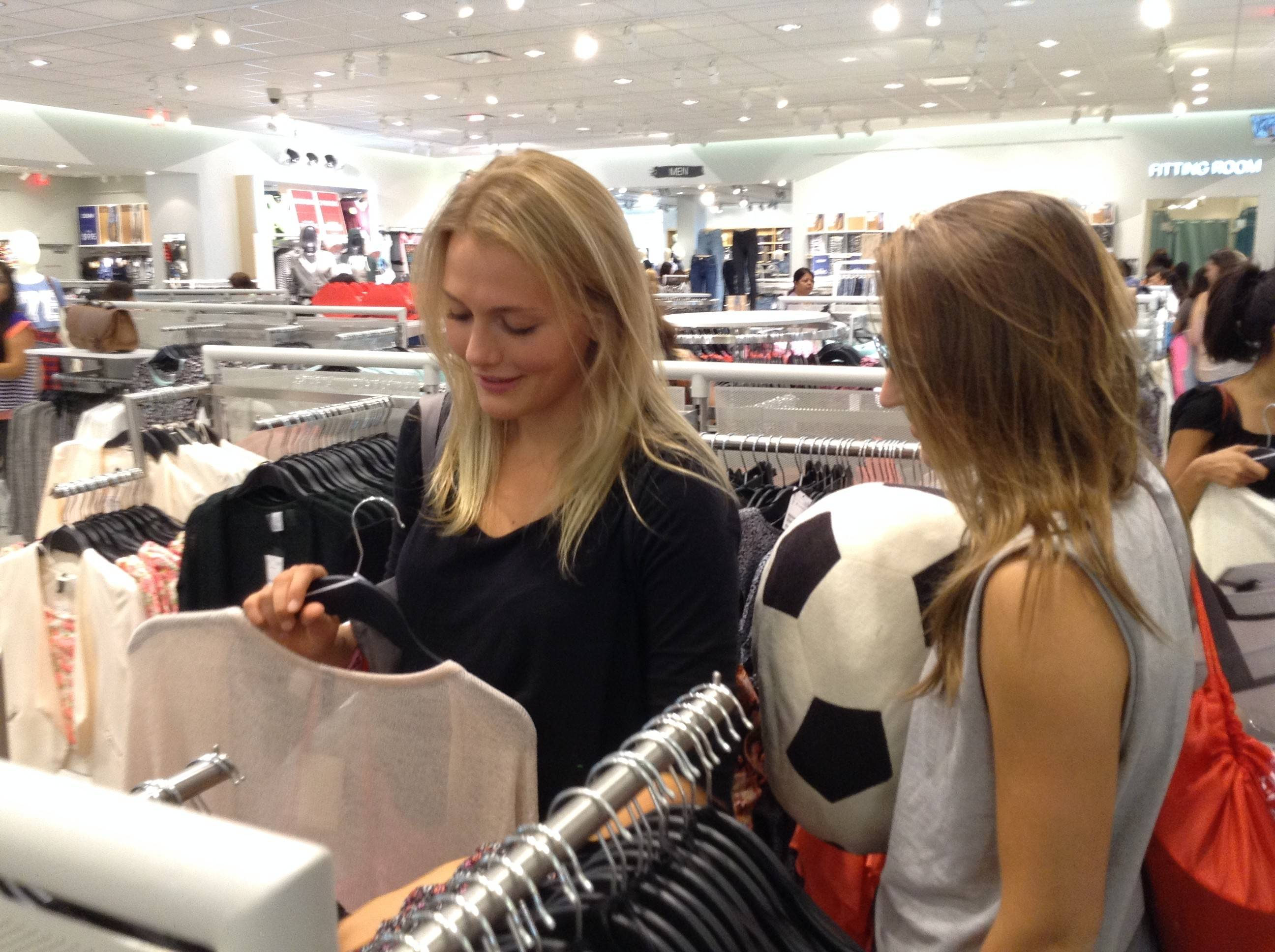 Kotryna Staputyte, left, and Paige Hochstatter of Naperville browse clothing at a new H&M that opened Thursday at Yorktown Center in Lombard. The two women waited in line for about three hours to be among the first customers.