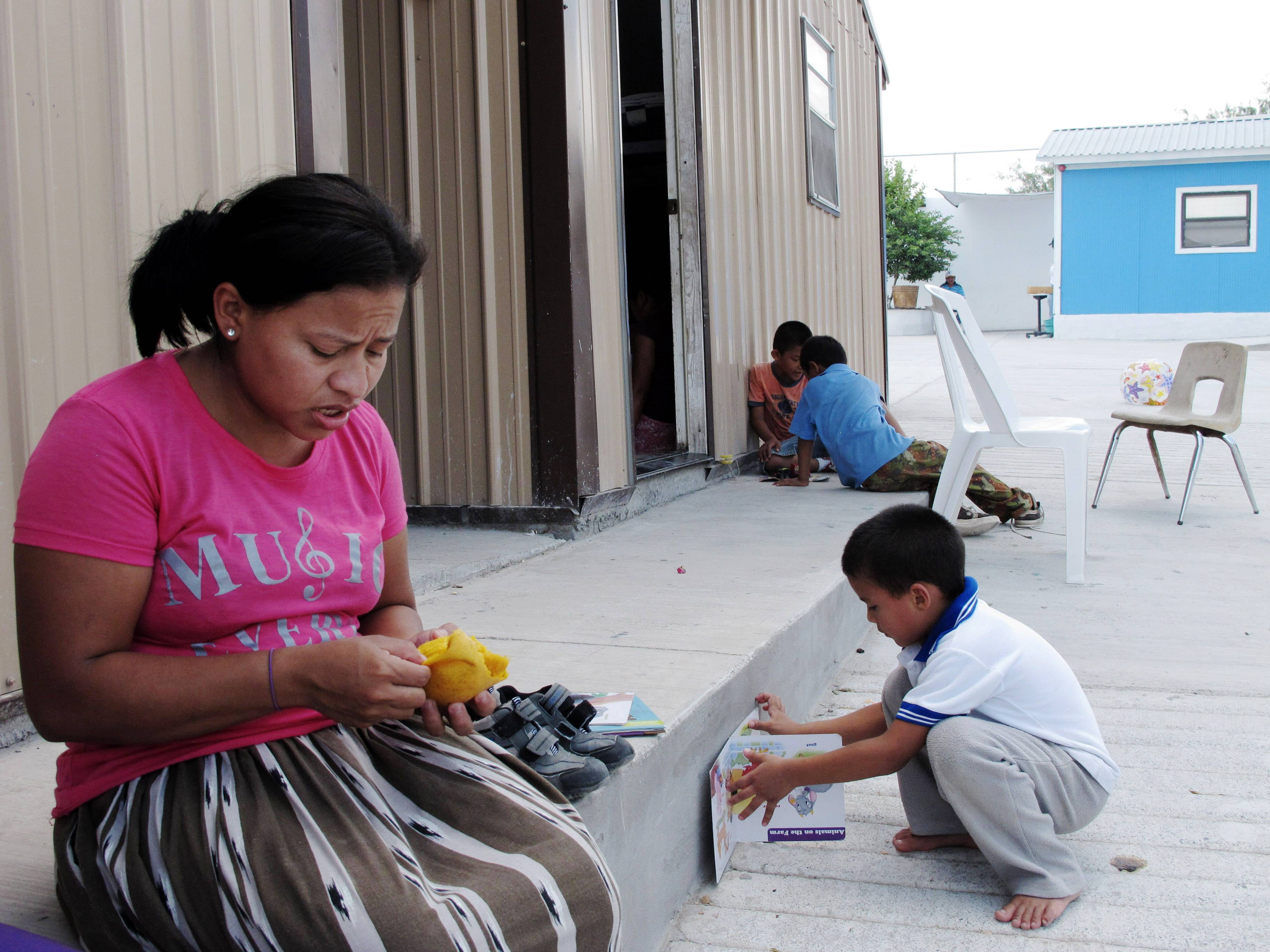 This Aug. 4, 2014 photo shows Eneyda Alvarez of Honduras peeling a mango while her son Antony plays at the Senda de Vida migrant shelter in Reynosa, Mexico. Alvarez hopes to join the thousands of families _ mothers or fathers with young children _ who have crossed the Rio Grande into the U.S. United States.