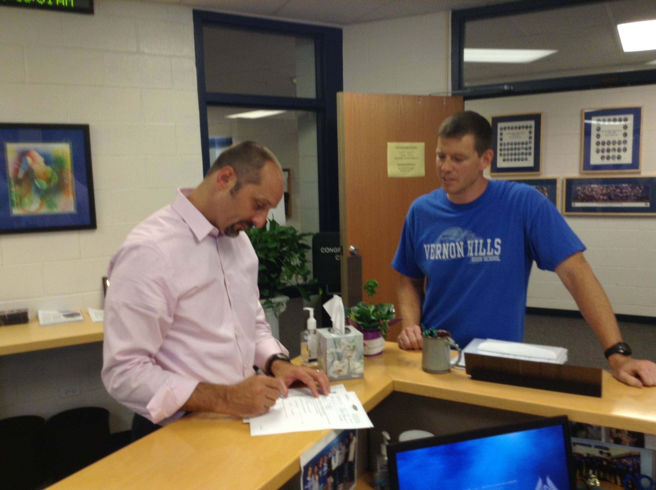 Vernon Hills High School Principal Jon Guillaume, left, signs paperwork for teacher and coach Ross Caton. Guillaume started as principal July 1.