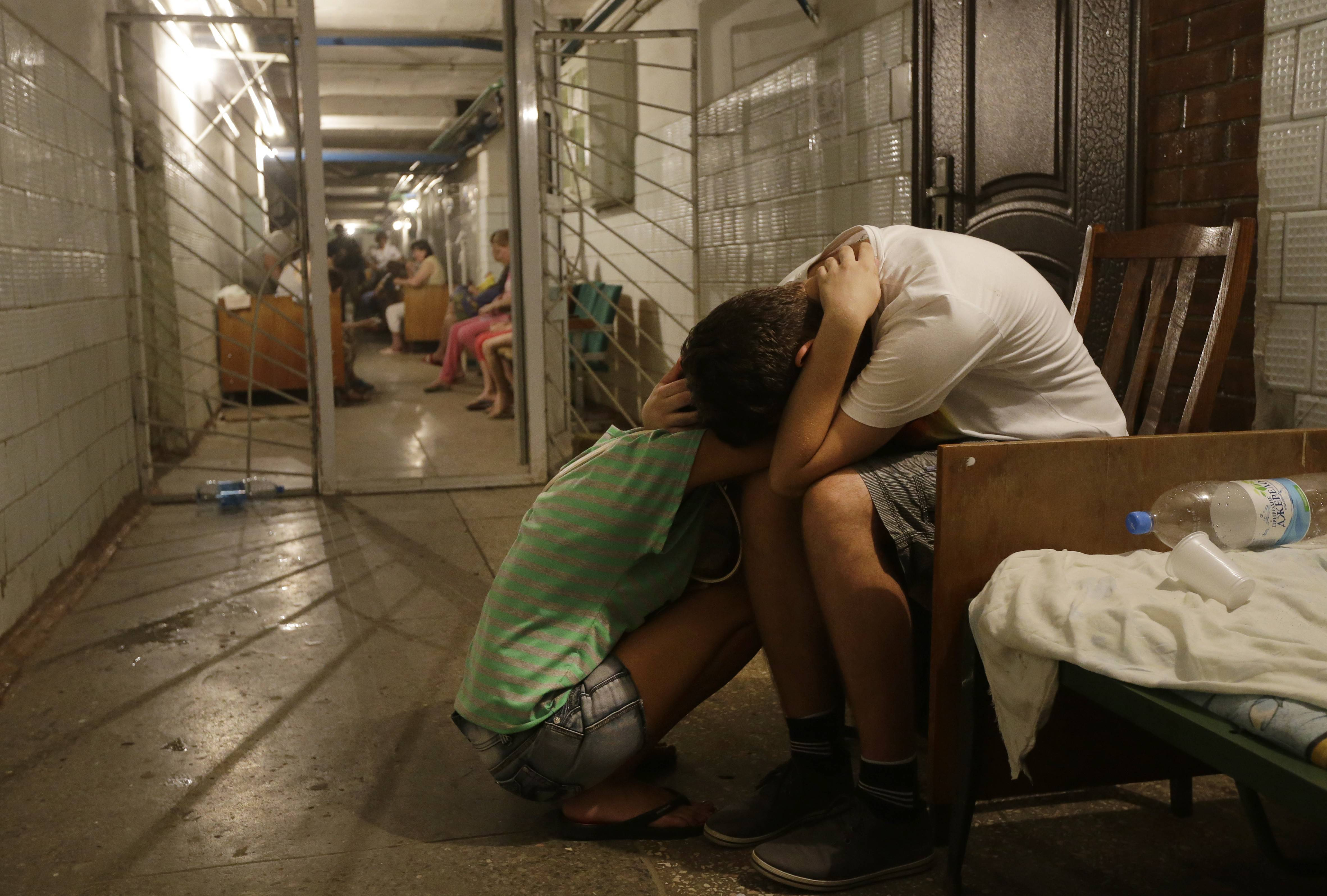 Local residents cry and hug each other as they sit in a hospital basement being used as a bomb-shelter after shelling, in Donetsk, eastern Ukraine, Thursday, Aug. 7, 2014. Fighting in the rebel stronghold of Donetsk claimed more civilian casualties, bringing new calls from Russian nationalists for President Vladimir Putin to send in the army.
