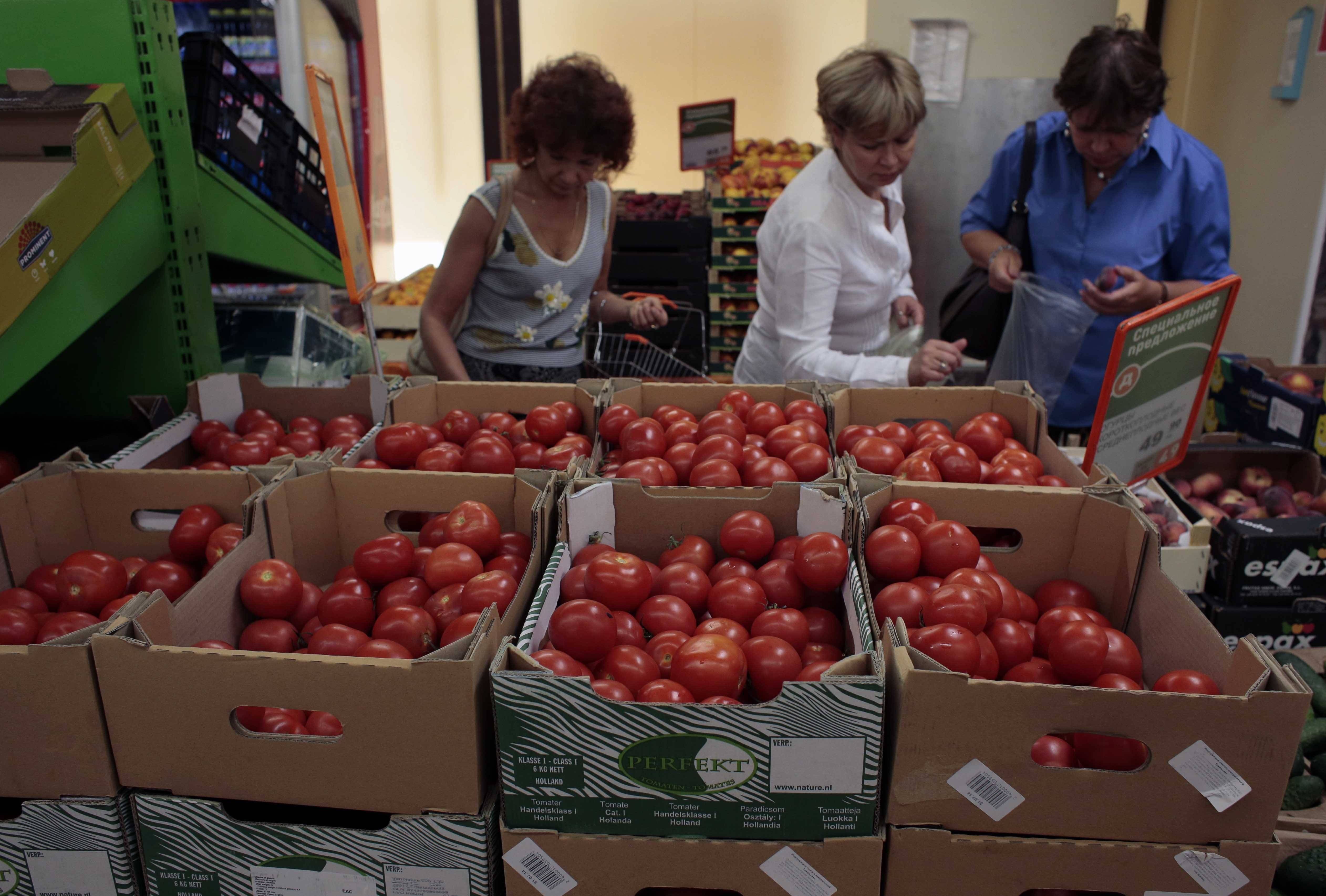 Women choose Dutch tomatoes at a supermarket in downtown Moscow on Thursday, Aug. 7, 2014. The Russian government has banned all imports of meat, fish, milk and milk products and fruit and vegetables from the United States, the European Union, Australia, Canada and Norway, Prime Minister Dmitry Medvedev announced Thursday.