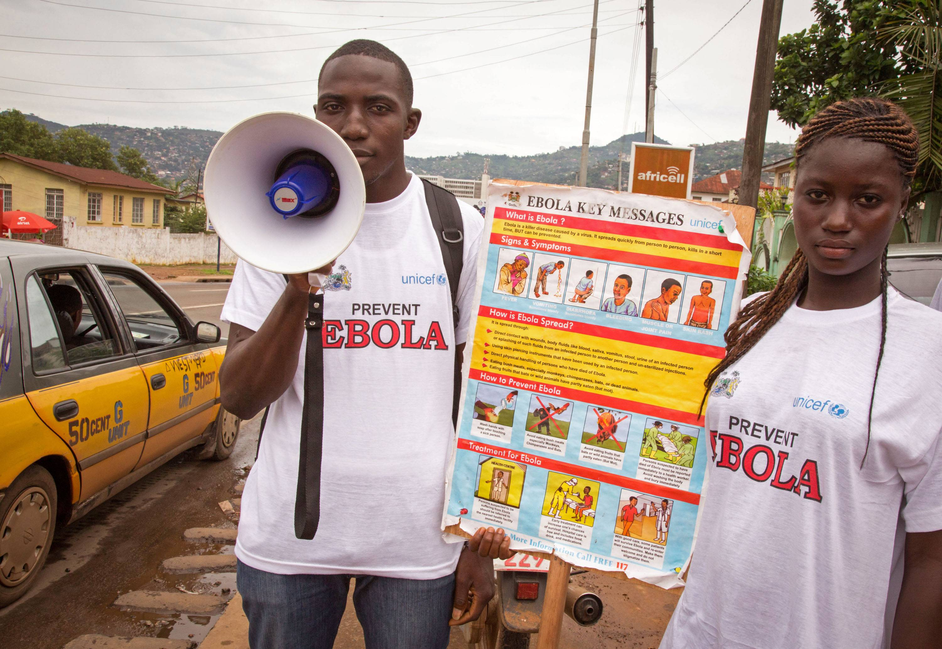 A man and woman taking part in a Ebola prevention campaign holds a placard with an Ebola prevention information message in the city of Freetown, Sierra Leone, Wednesday, Aug. 6, 2014.