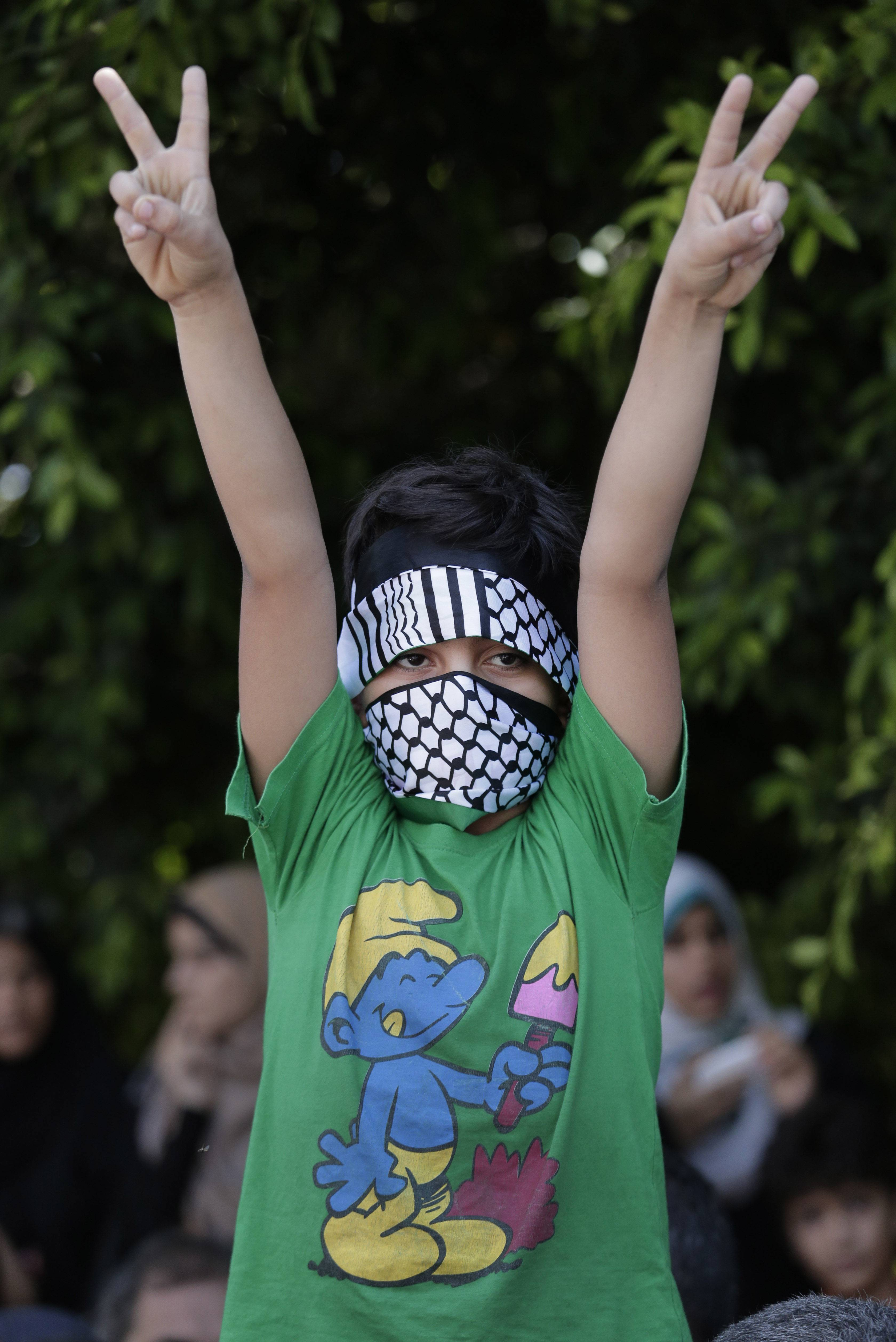 A Palestinian boy flashes the V-sign as he participates in a Hamas rally in Gaza City, Gaza Strip, Thursday, Aug. 7, 2014. Thursday's rally drew several thousand supporters and a senior Hamas official has told supporters at the rally that the war with Israel won't be over until the group's political demands are met.