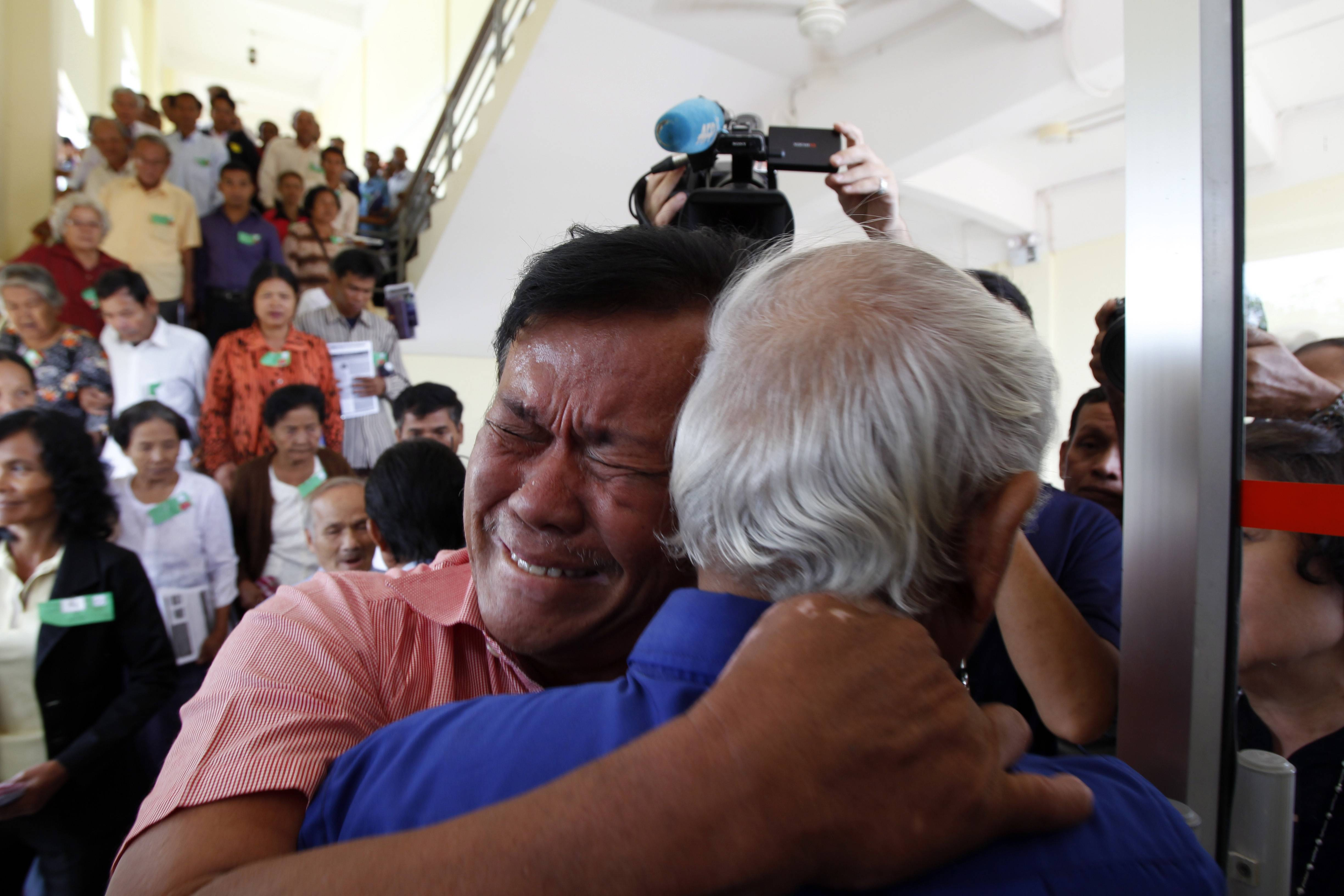 Cambodian former Khmer Rouge servitors, Soum Rithy, left, cries as he hugs Chum Mey, right, after the verdicts were announced, at the U.N.-backed war crimes tribunal in Phnom Penh, Cambodia, Thurdday, Aug. 7, 2014. Three and a half decades after the genocidal rule of Cambodia's Khmer Rouge ended, the tribunal on Thursday sentenced two top leaders of the former regime to life in prison on war crimes charges for their role in the country's terror period in the 1970s.