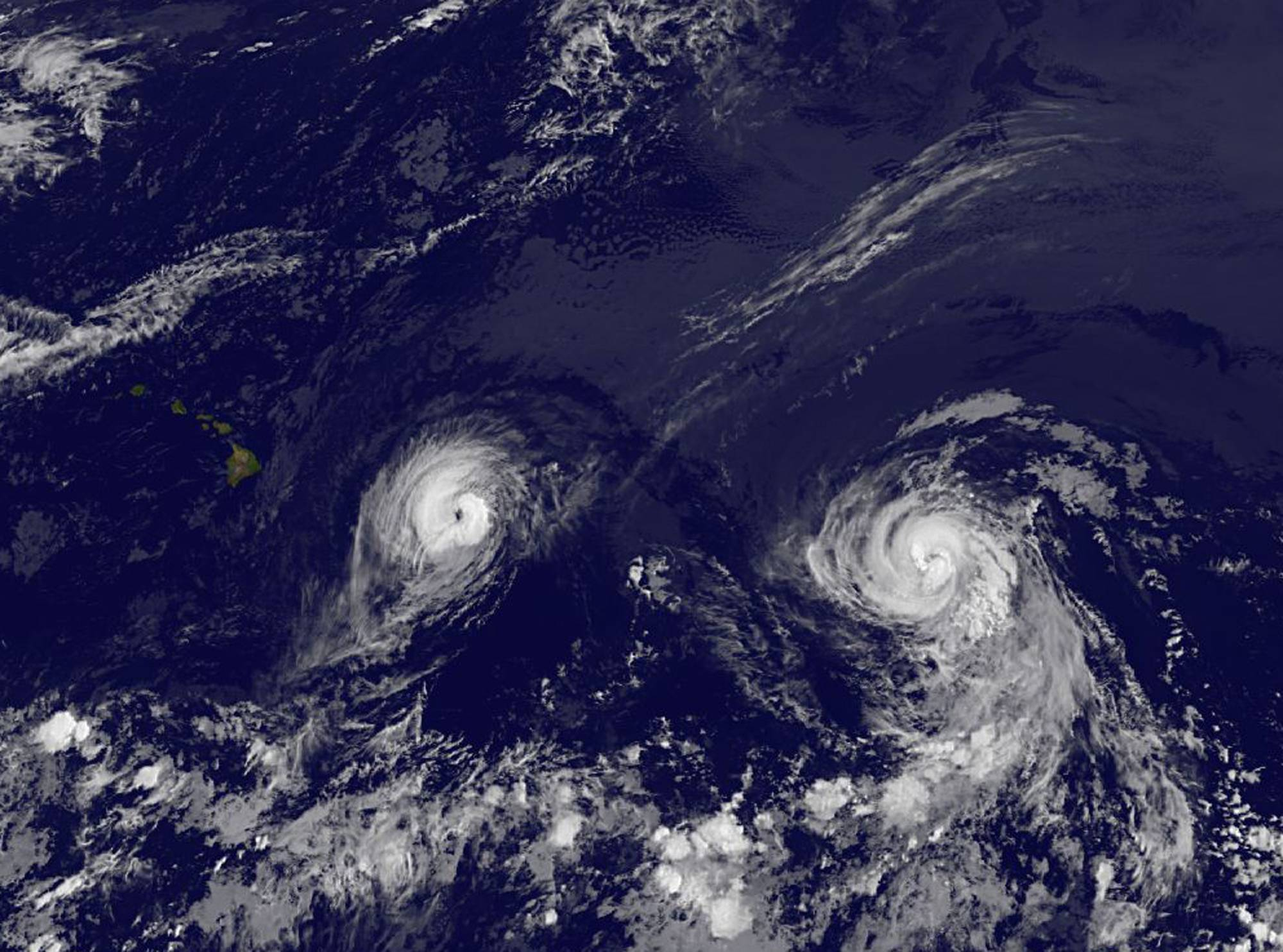 This image provided by NOAA taken Thursday Aug. 7, 2014 at 2 a.m. EDT shows Hurricane Iselle, left and Hurricane Julio. Iselle was supposed to weaken as it slowly trudged west across the Pacific. It didn't -- and now Hawaii is poised to take its first direct hurricane hit in 22 years. The center of Hurricane Iselle is expected to pass very near or over the Big Island Thursday night and just south of the smaller islands Friday. Some weakening is forecast during the next 48 hours however Iselle is still expected to be near hurricane strength as it impacts the Big Island.