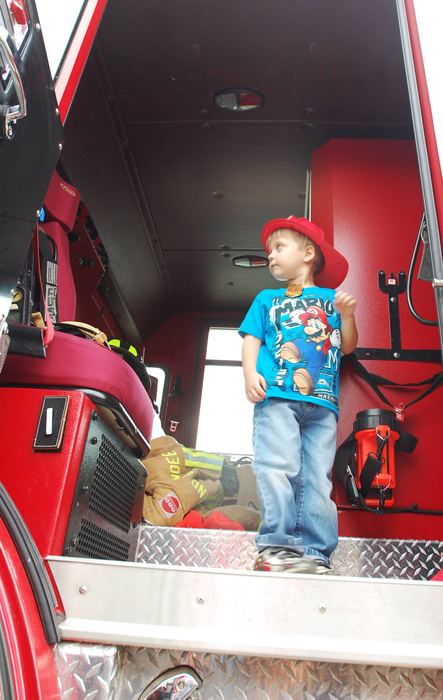 Mason Wayeshe, 5, of Elgin surveys his surroundings from the doorway of a fire truck at last year's Corn Roast fundraiser at Randy´s Vegetables in Sleepy Hollow. Randy's teamed with the Sleepy Hollow Police Department to raise money for Special Olympics Illinois.
