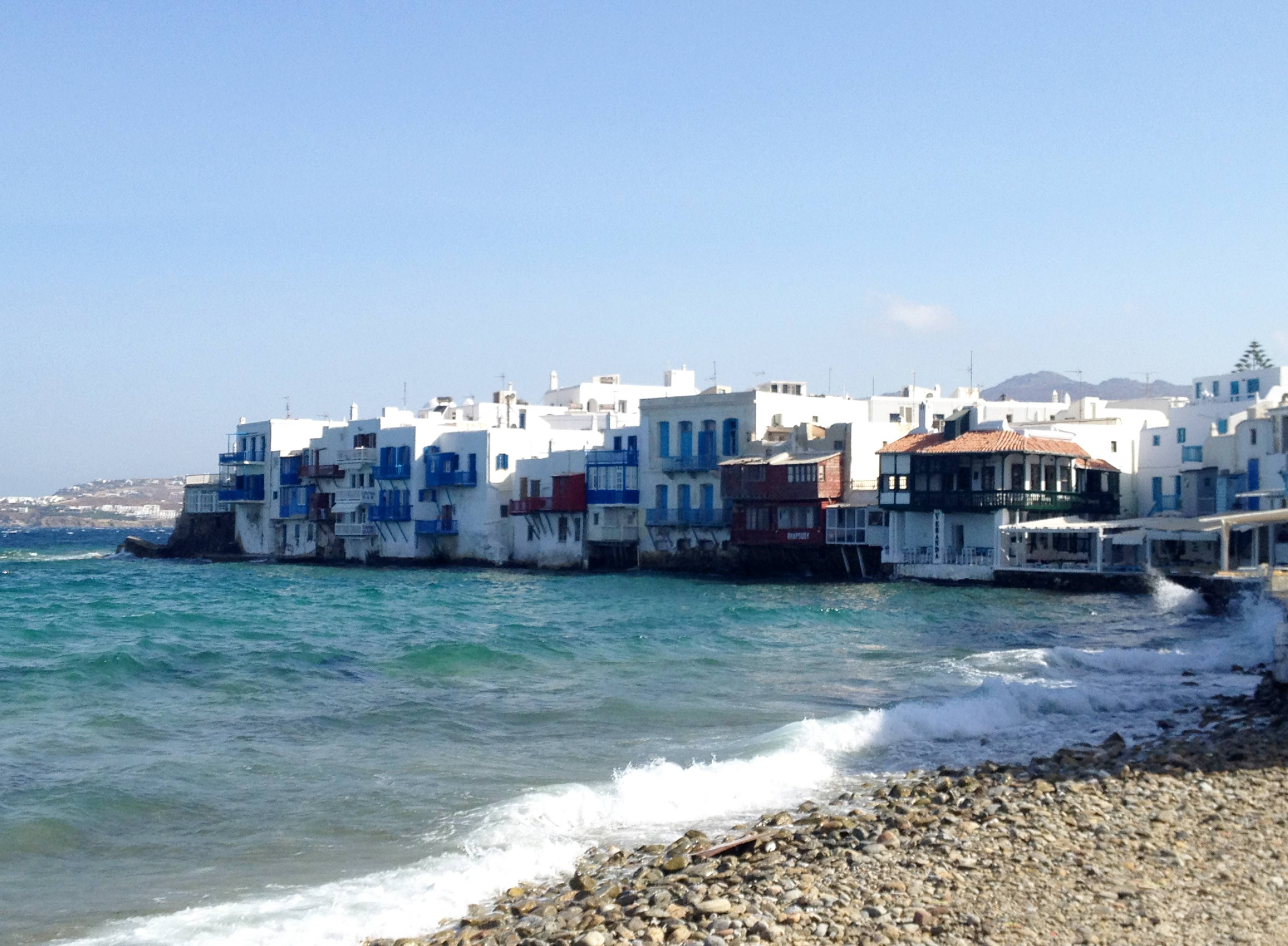 Visitors enjoy black-sand beaches and a view of the homes tucked into the waterfront of the island of Mykonos, in an area known as Little Venice. Mykonos is located in the Cyclades, a Greek island chain in the Aegean Sea.