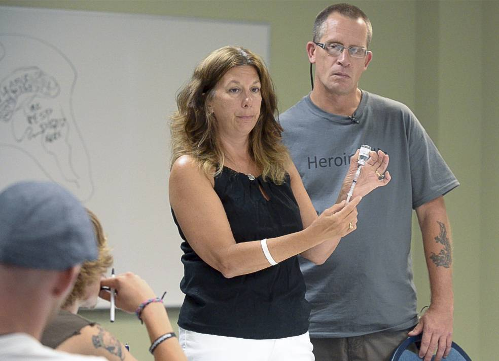 Caroline Kacena, whose son died from a heroin overdose, and Tim Ryan, who himself is a recovering heroin addict who just lost his son Nick to a heroin overdose last week, demonstrate how to use Naloxone during Thursday's training session at Wheatland Salem Church in Naperville.