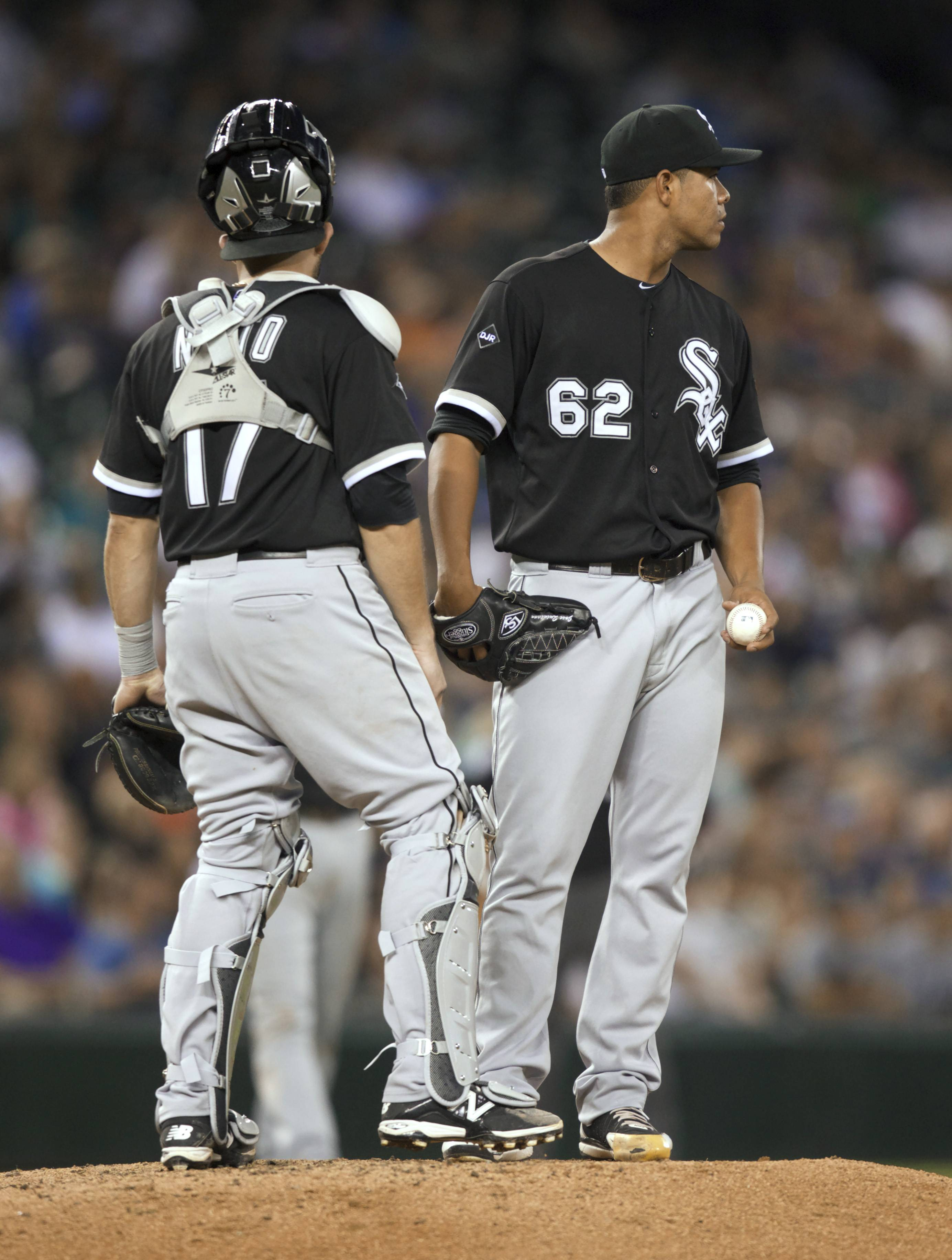 Chicago White Sox starter Jose Quintana (62) meets at the mound with catcher Adrian Nieto before Quitana was replaced during the sixth inning of a baseball game against the Seattle Mariners, Friday, Aug. 8, 2014, in Seattle. (AP Photo/Stephen Brashear)