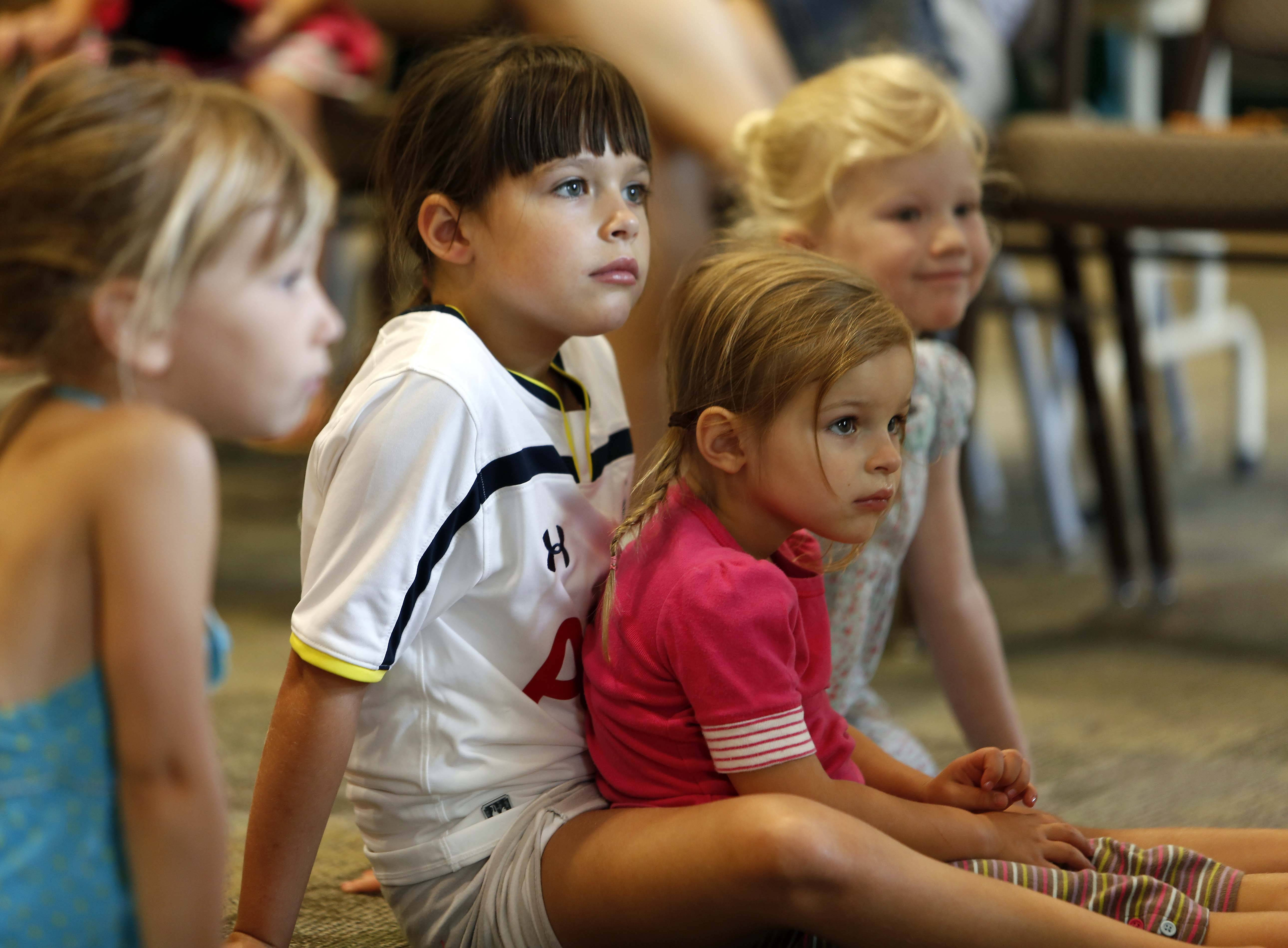 Seven-year-old Maggie Krause, center, of Oak Brook, holds her sister Hannah, 3, on her lap while listening to the stories.