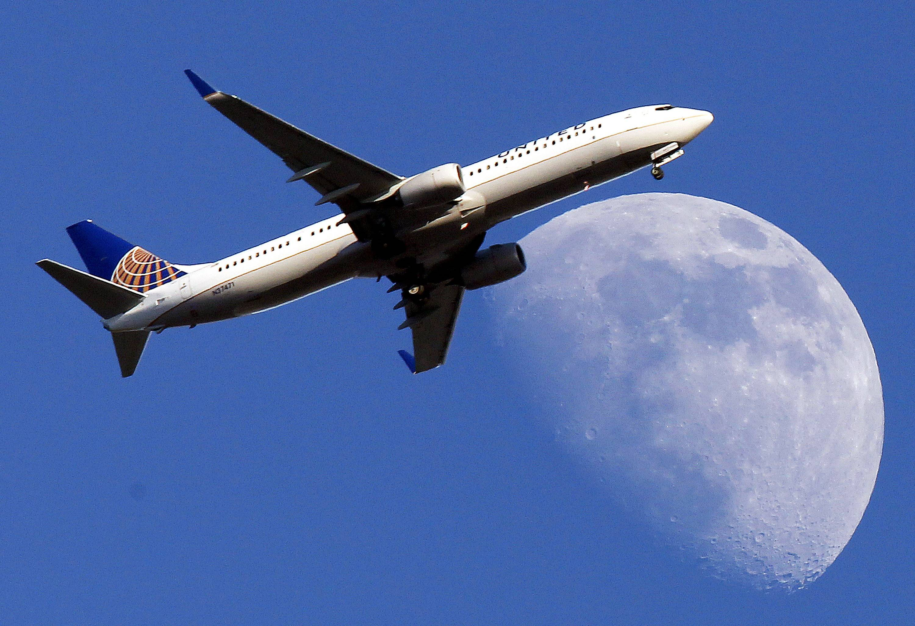 A United Airlines jet approaching Los Angeles International Airport passes in front of a Waxing Gibbous moon.