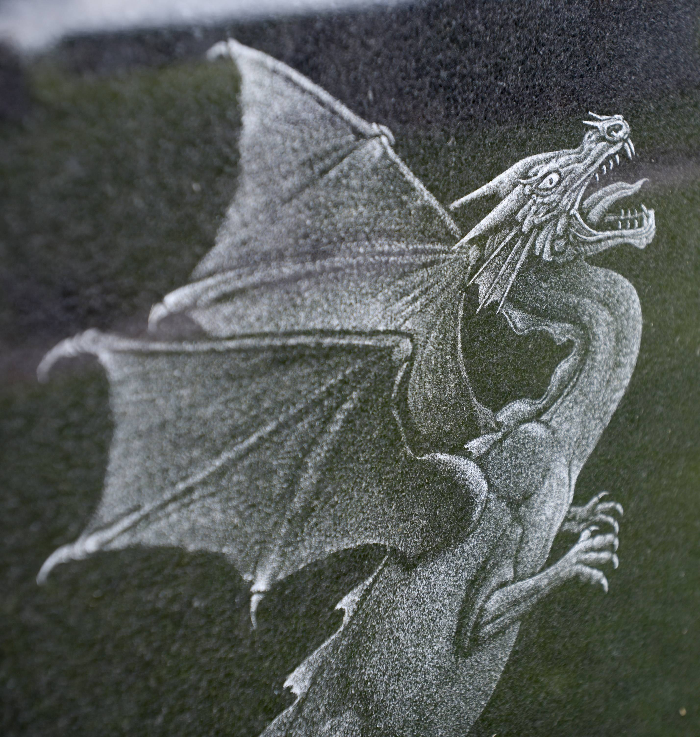 Customers sometimes ask for unique images to be placed on the marker of a loved one. Shoaf hand-etched this dragon into a black granite grave maker.