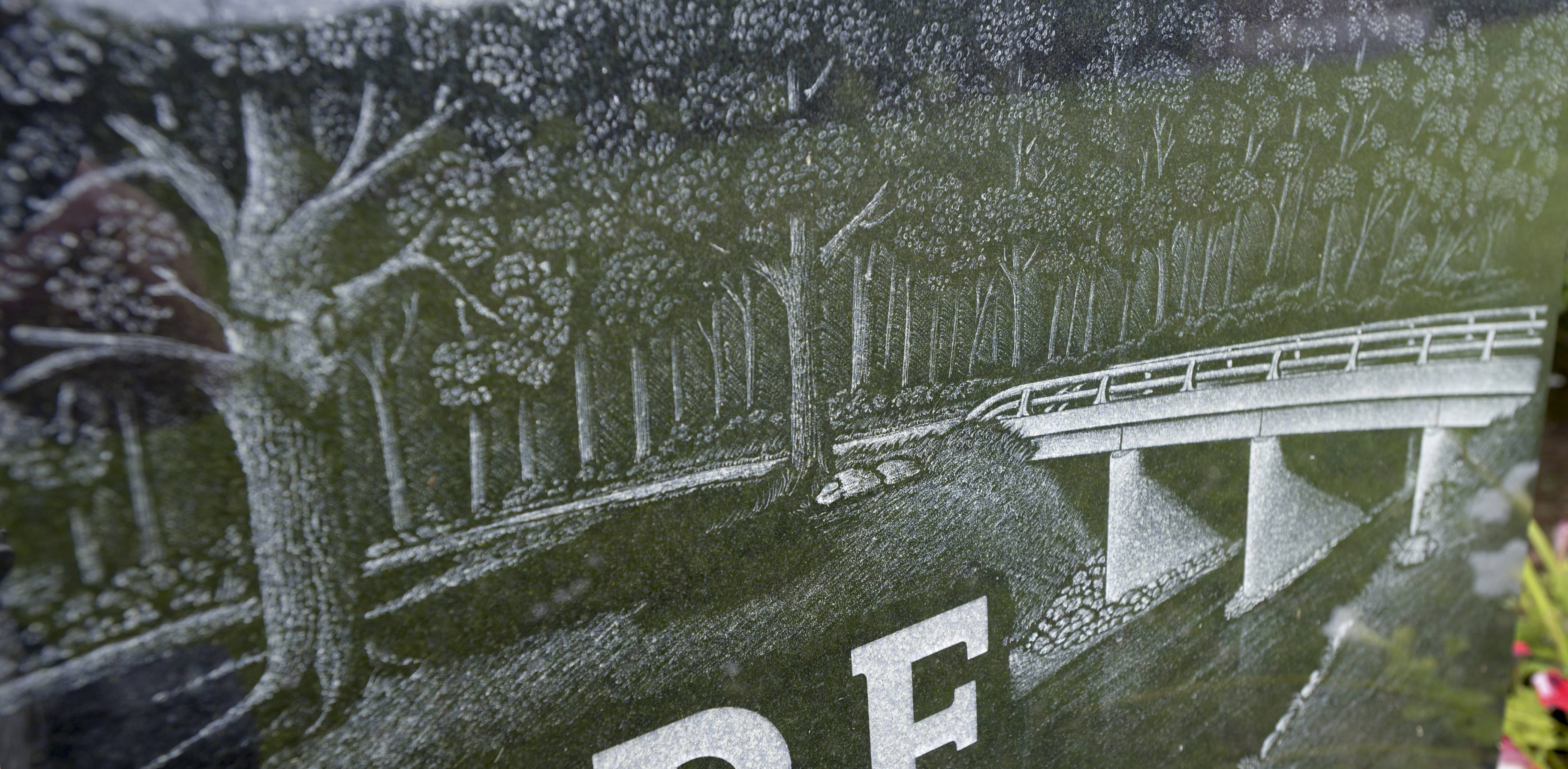 Jim Shoaf etched this nature scene and bridge on a marker at the request of a widow whose husband was a bridge builder.
