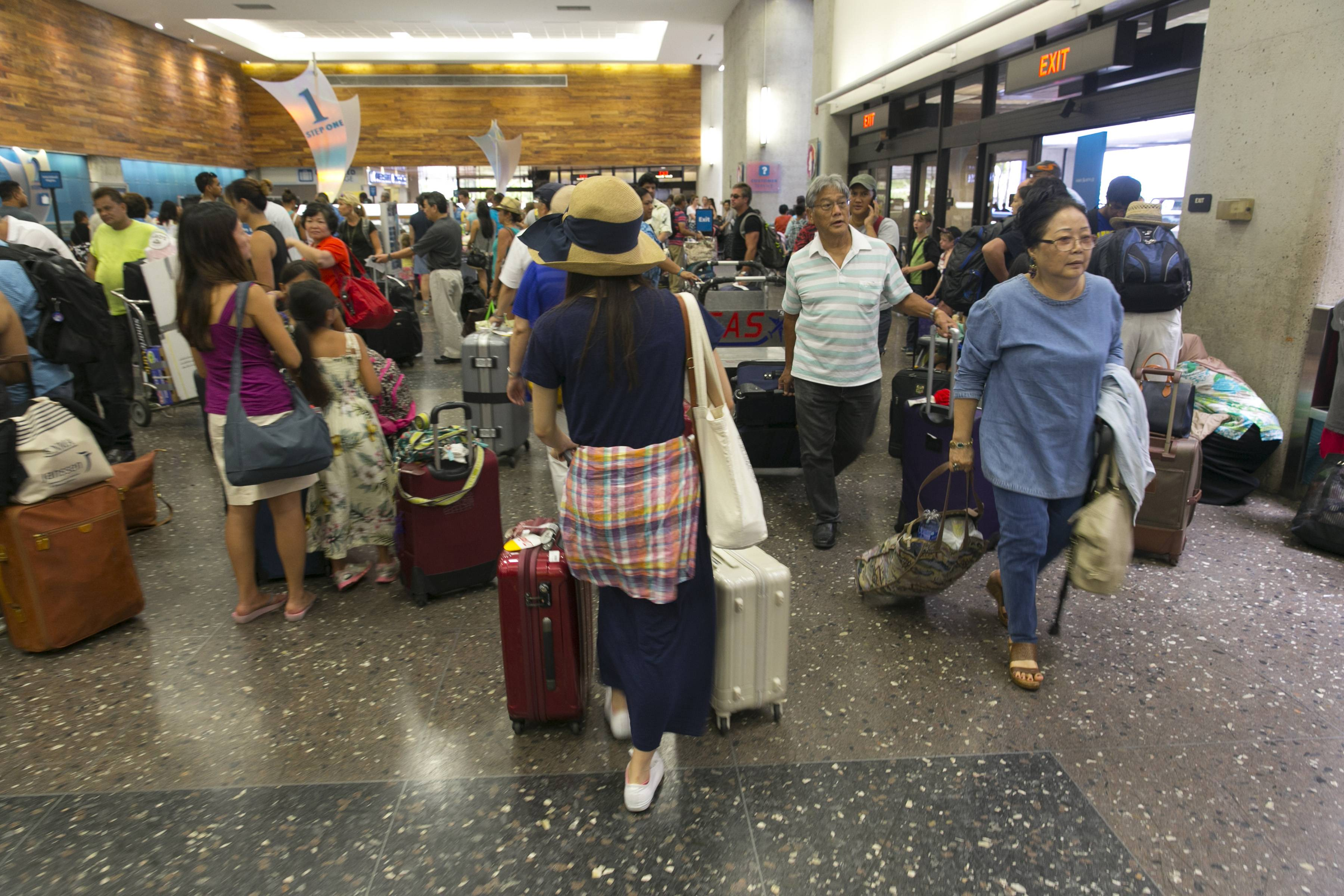 Crowds line up inside the departures terminal at the Honolulu International Airport in Honolulu on Thursday, Aug. 7, 2014. Hawaiian Airlines announced Thursday they are waiving change fees for passengers trying to leave before the storms hit the islands.