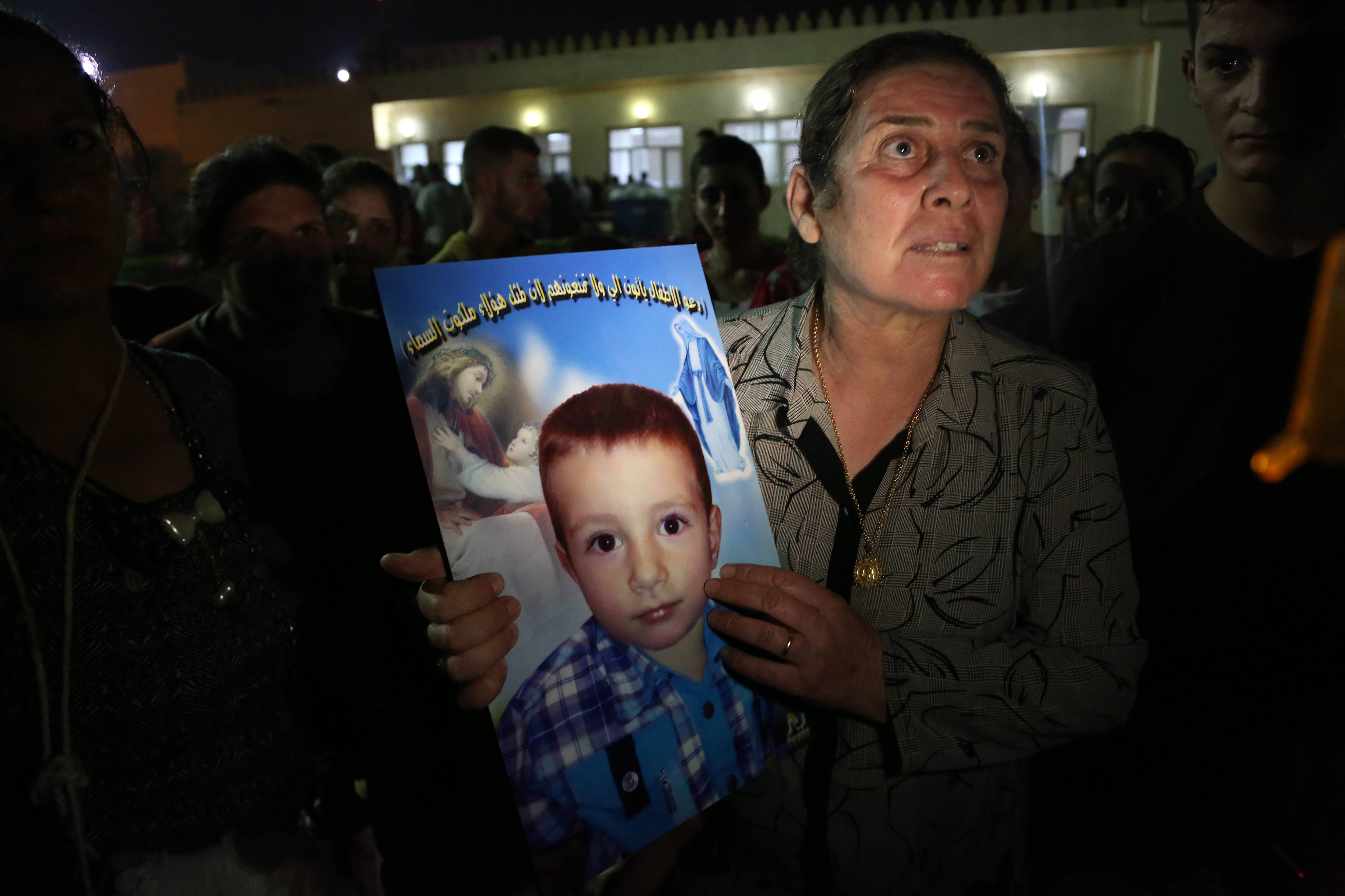 A displaced Iraqi Christian woman holds a picture of her four-year-old relative, David, who was killed by militants, at St. Joseph Church in Irbil, northern Iraq, Thursday, Aug. 7, 2014.